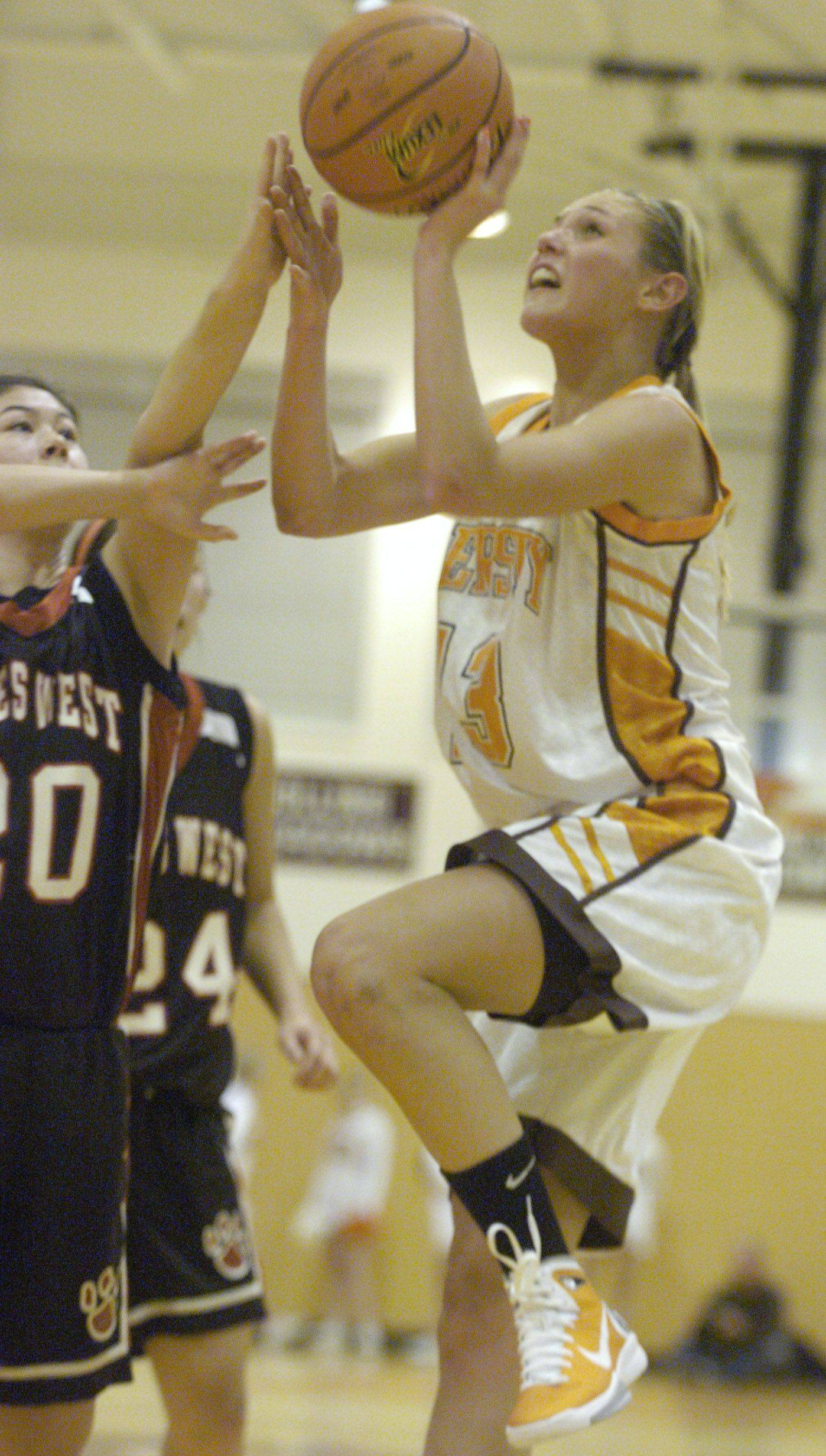 Hersey's Stefanie Mueller drives to the basket against the defense of Niles West's Casey Nakawatase.