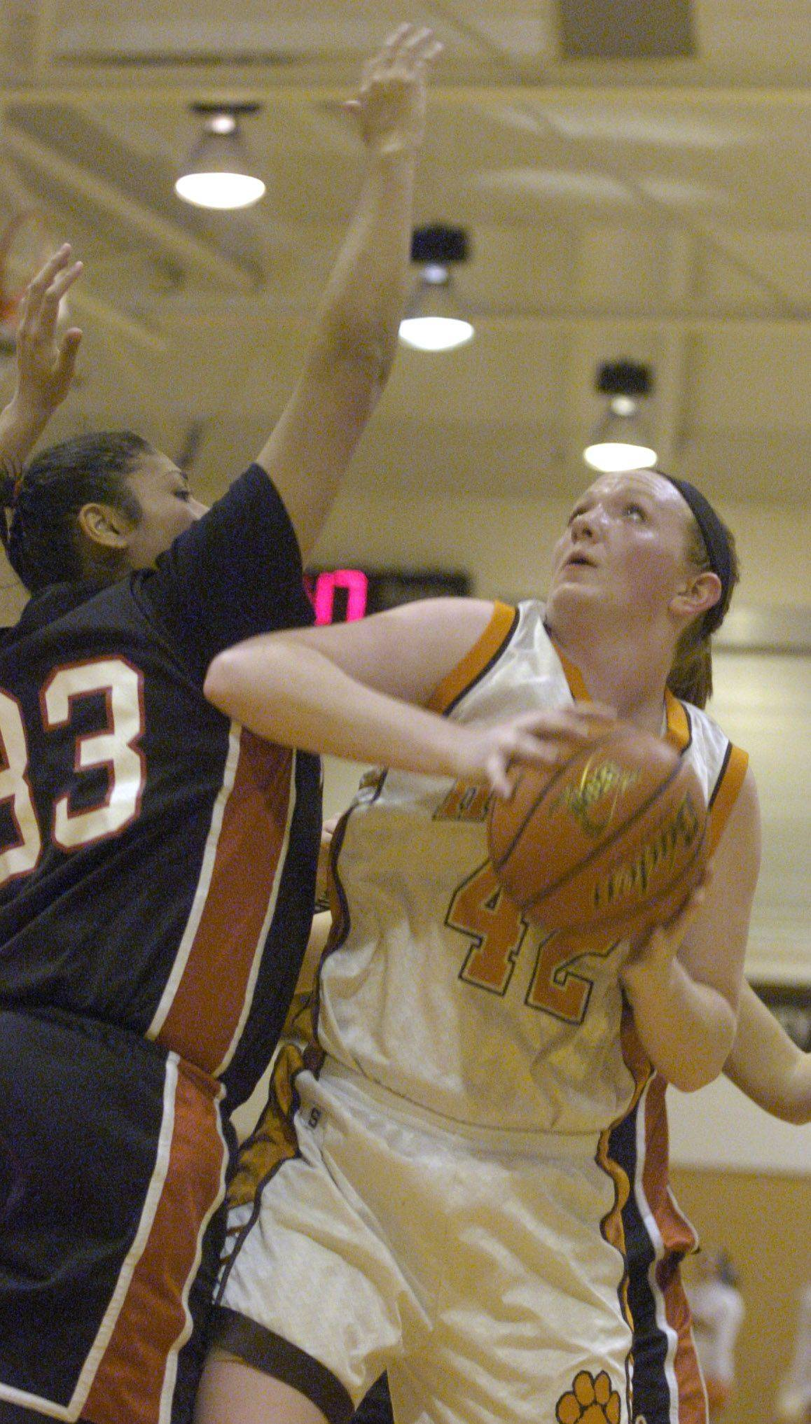 Hersey's Maggie Hogen, right, makes a strong move to the basket against Niles West's Jackie Cardenas.