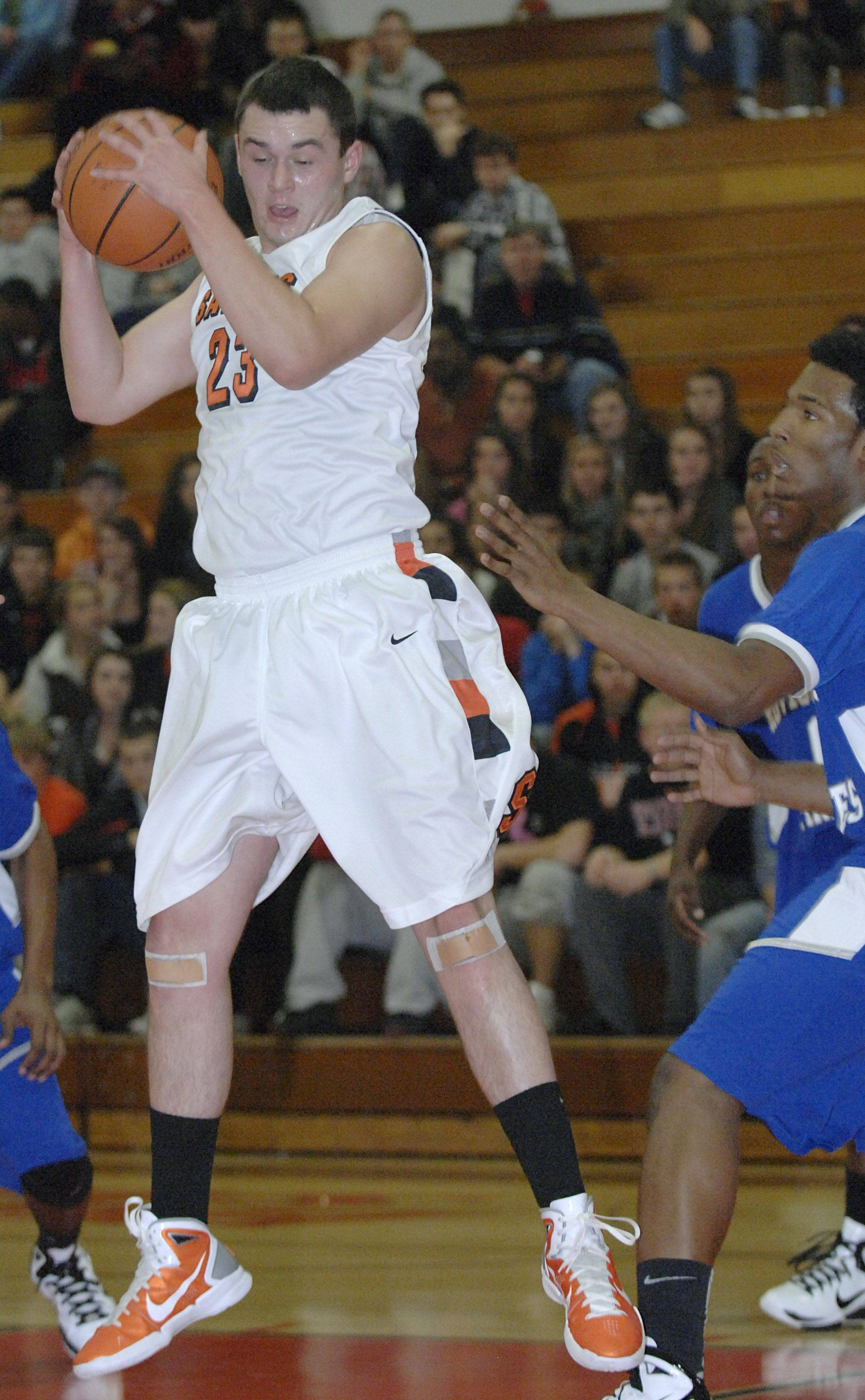 St. Charles East's Johnny Hondlik snatches a rebound in tournament game vs Proviso East on Tuesday, November 22.