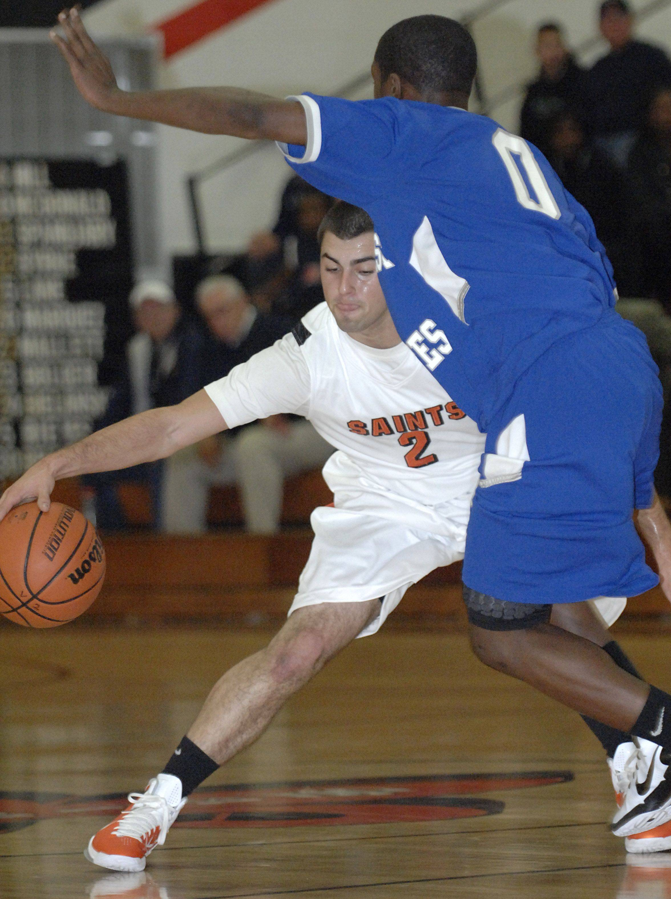 St. Charles East's Dan Ditusa attempts to dribble and pass around Proviso East's Keith Carter in the first quarter of tournament game on Tuesday, November 22.