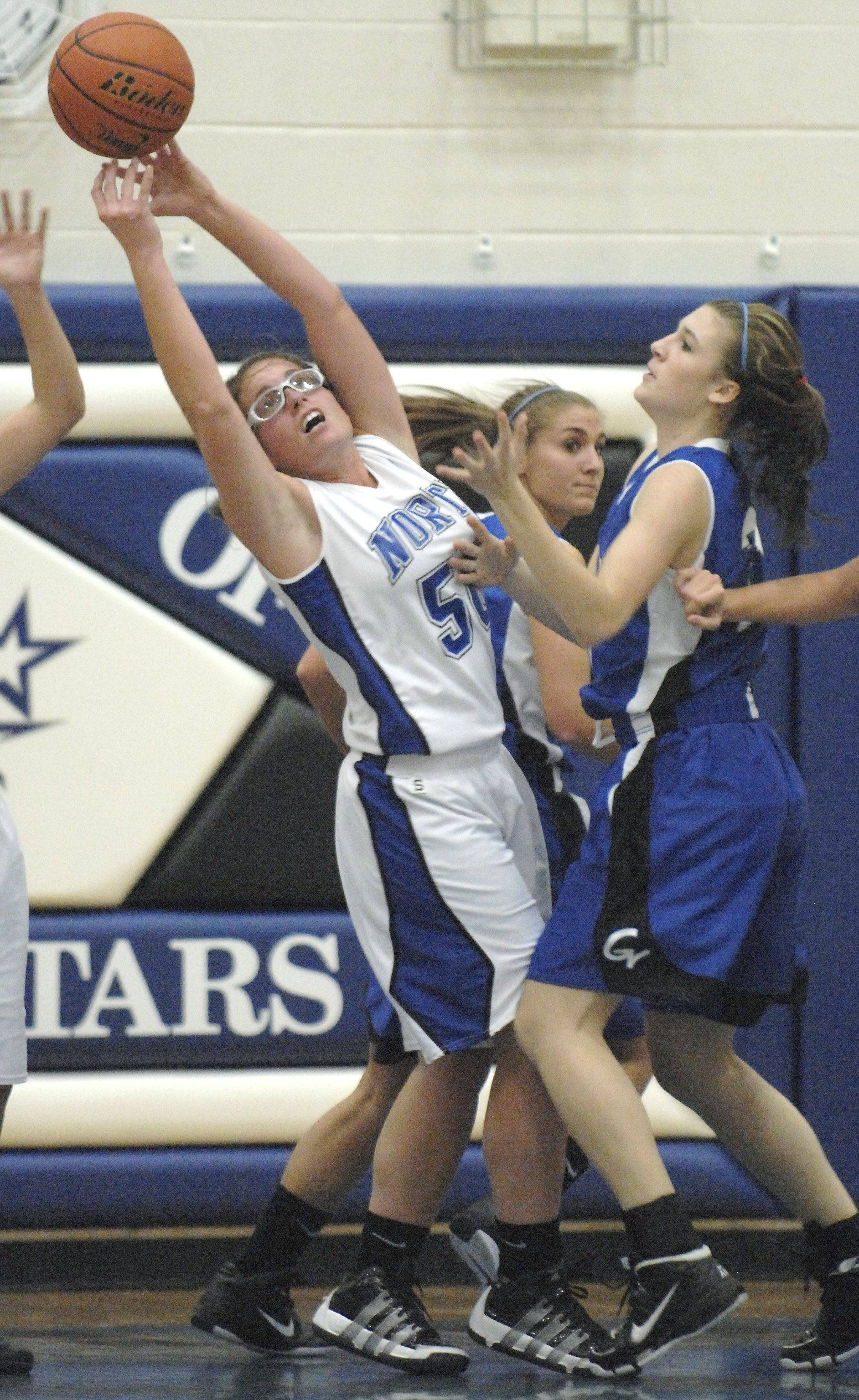 St. Charles North's Kate Booe battles for a rebound with Geneva's Sami Pawlak.