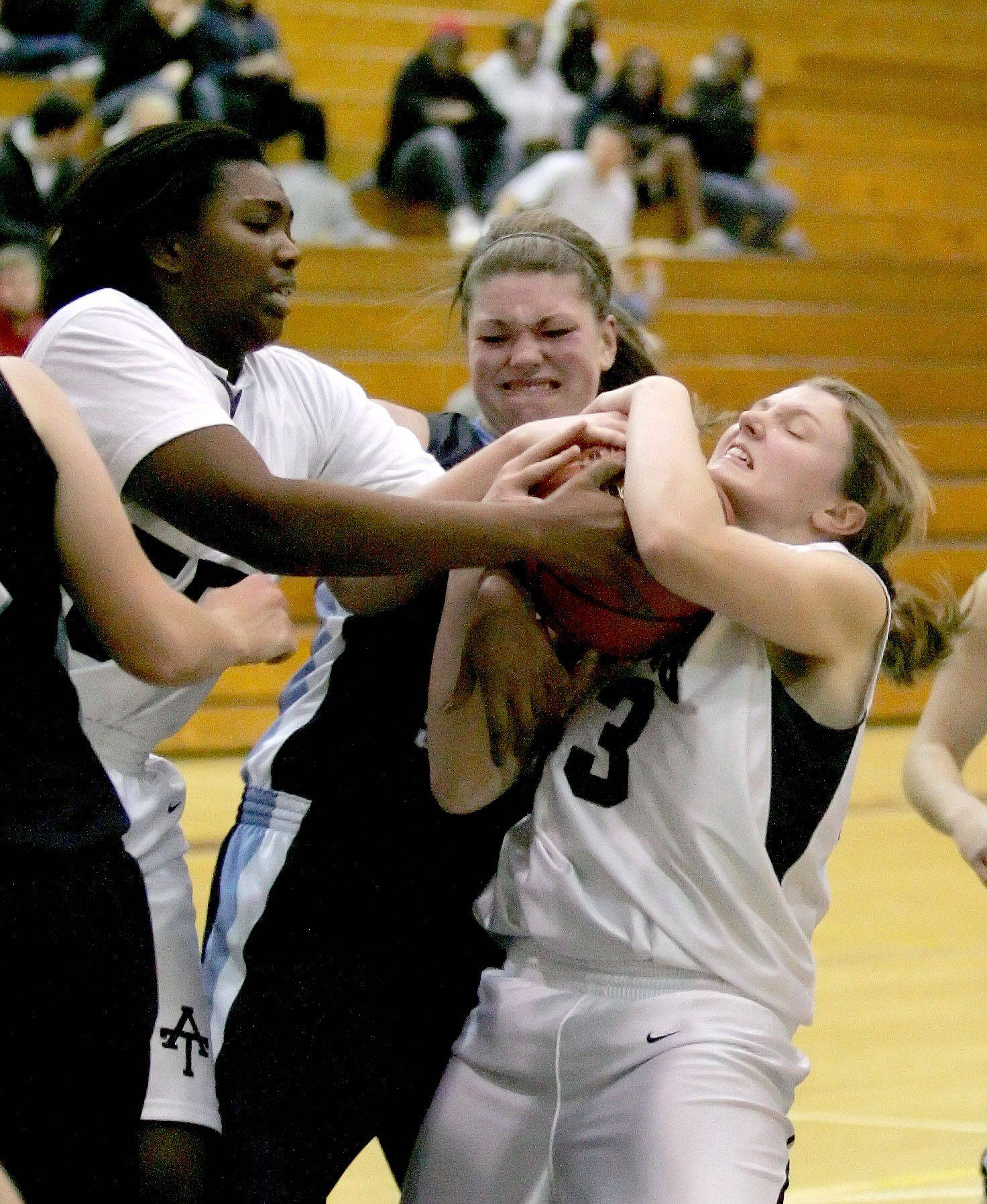 MeShaundra Donald, left, and Jamie Smolinski, right, of Addison Trail fight for the ball with Kirsten Zemke of Downers Grove South, center.