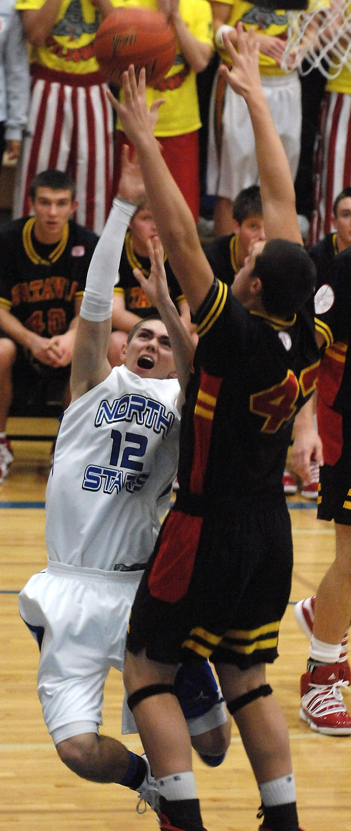 St. Charles North's Quinten Payne scores and is fouled by Batavia's Cole Gardner.