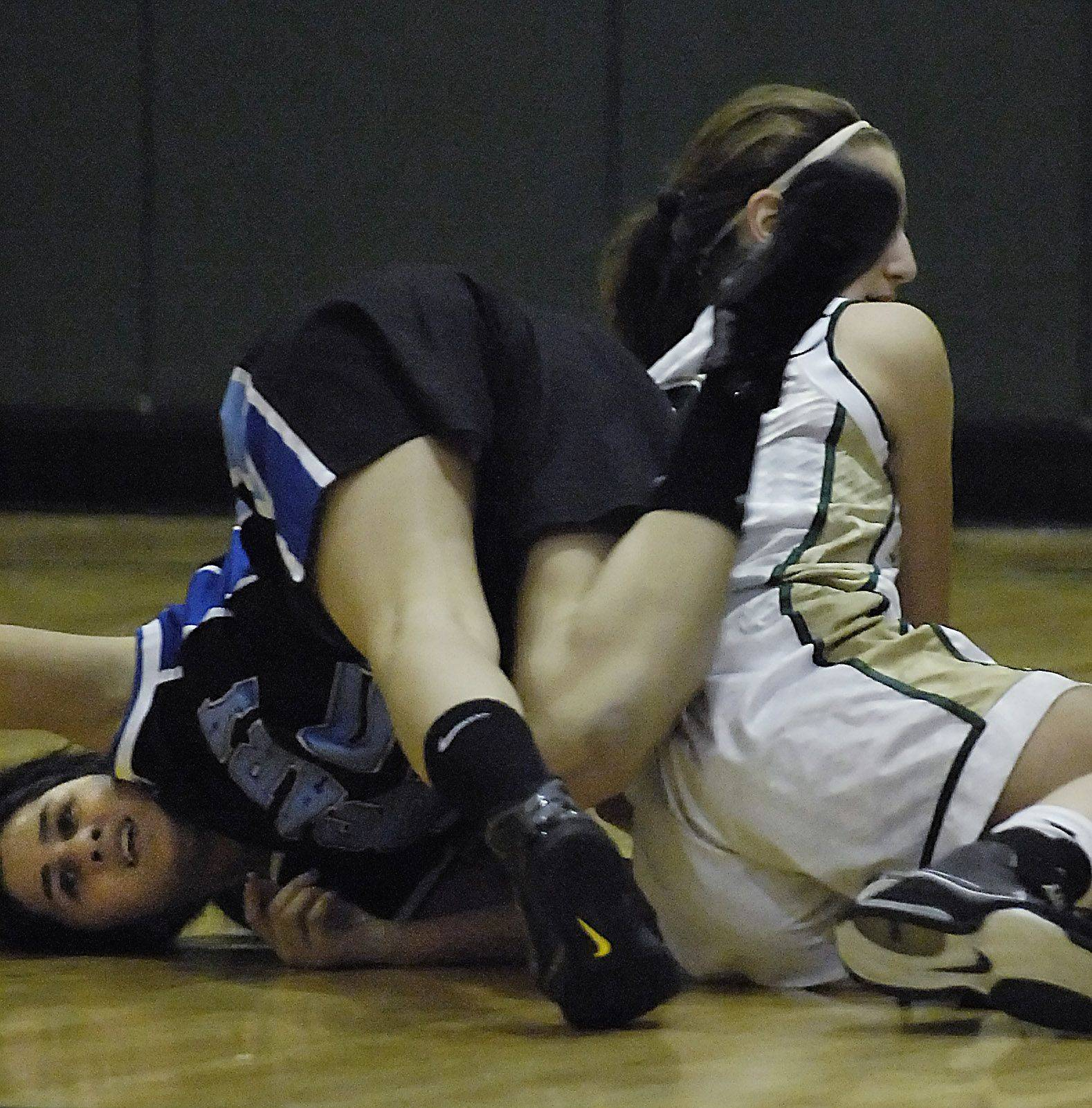 Rosary's Brenda Rocha ends up on her head as she fights for a loose ball with St. Edward's Rena Ranallo Thursday in Elgin.