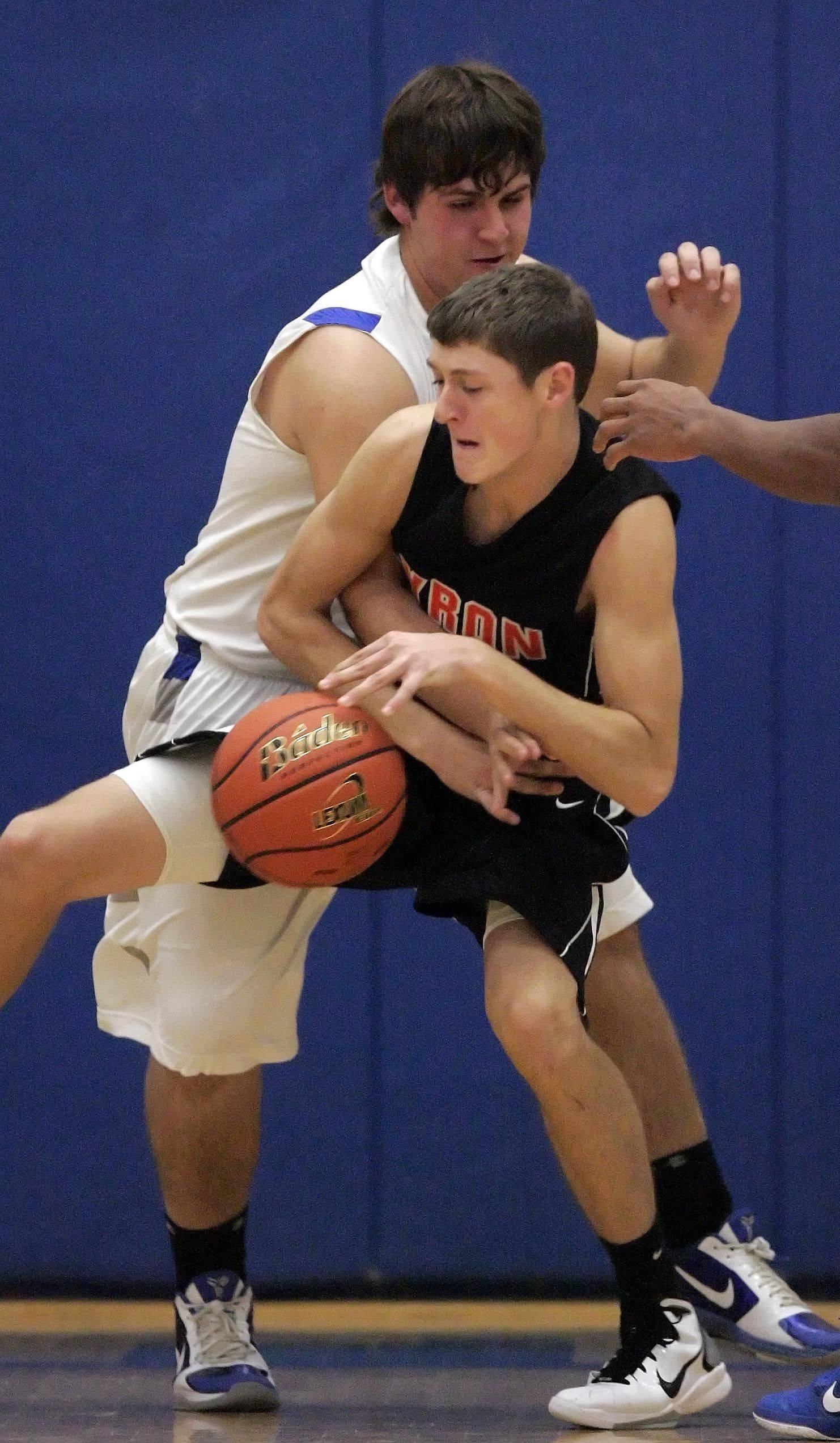 Burlington Central forward Joel Lopez wraps up Byron's Logan Crull.