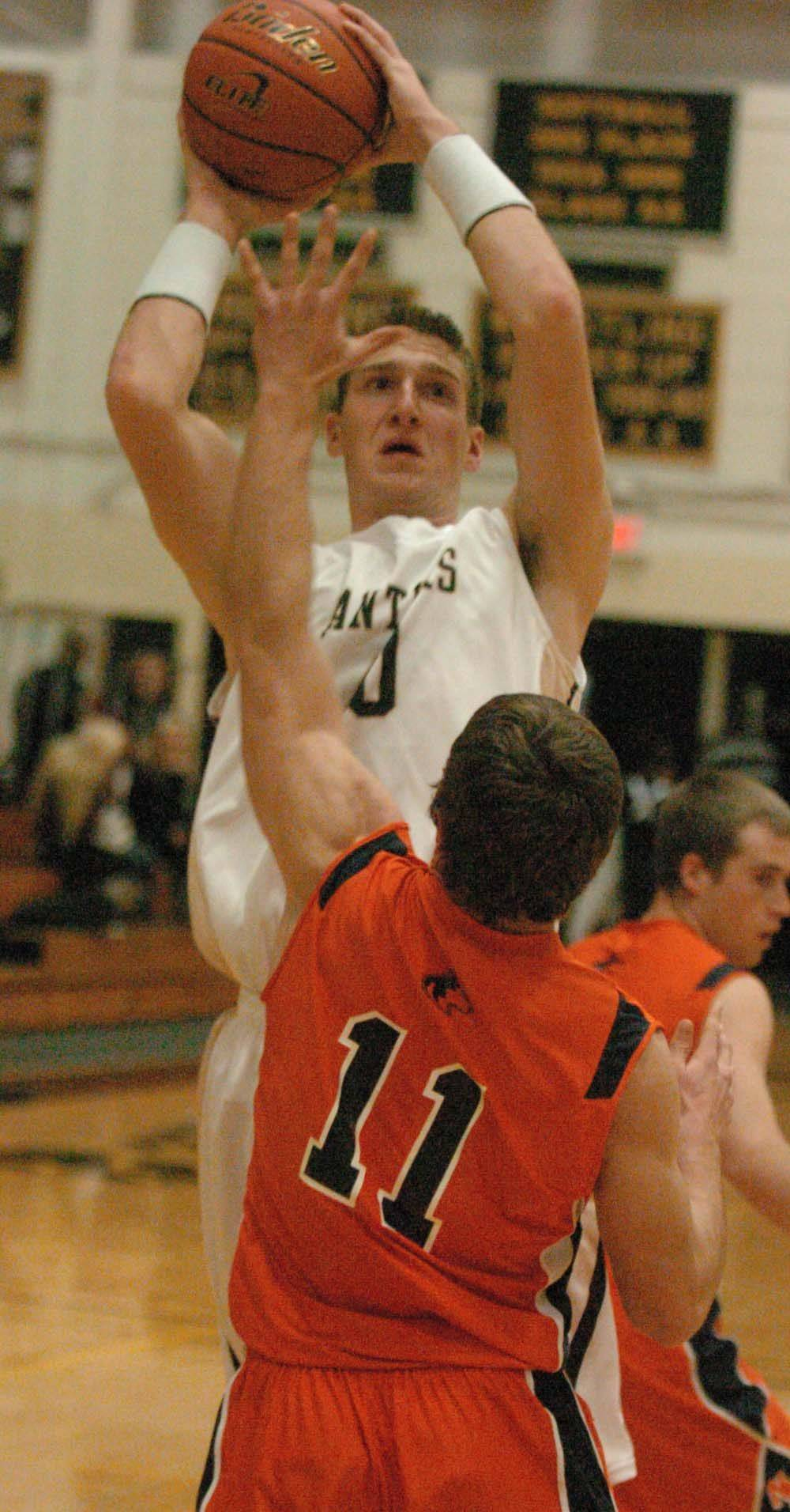 Matt Pemberton of Glenbard North goes up for a shot while Tim Davis of Naperville North tries to block.