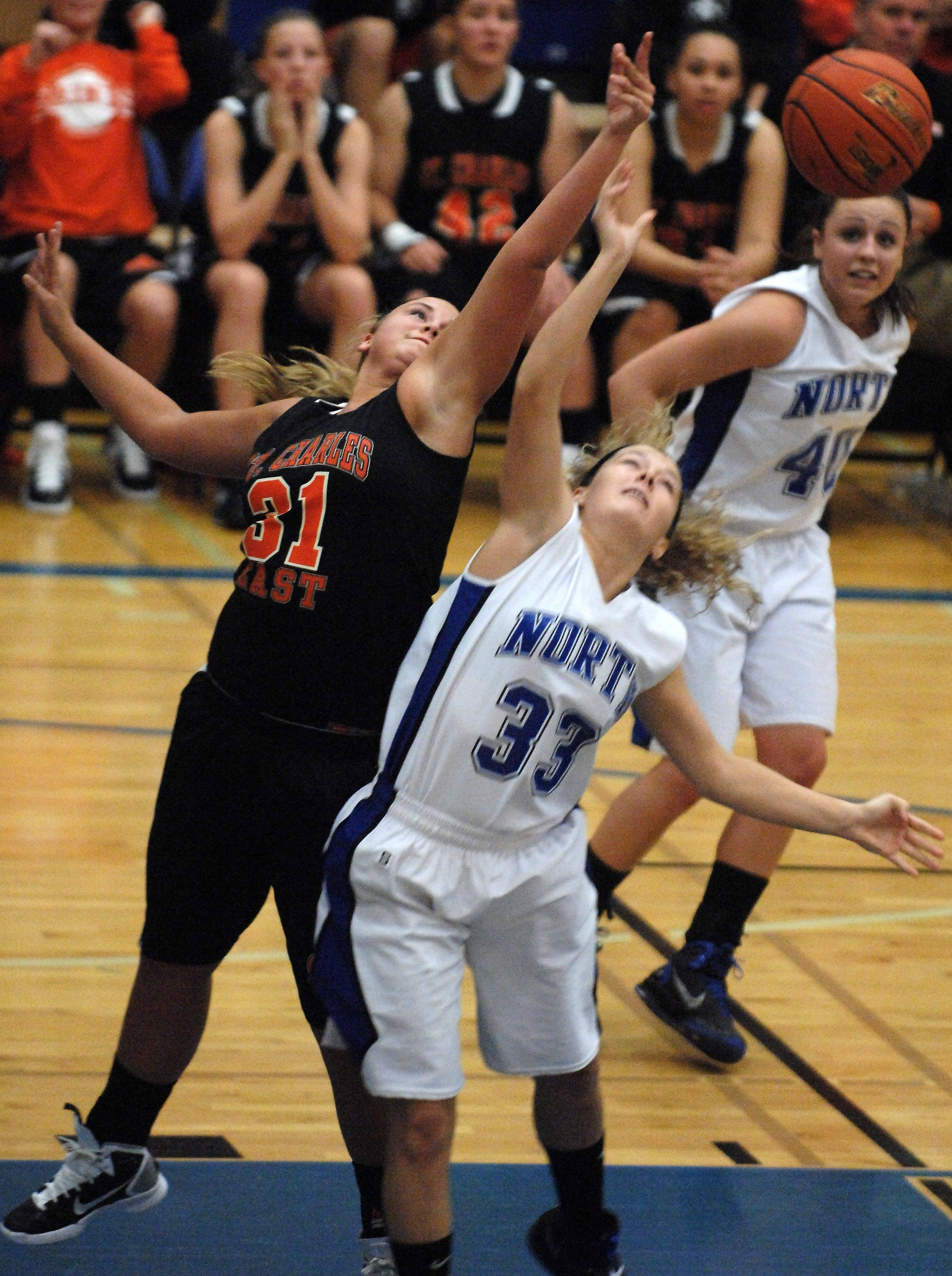 St. Charles East forward Morgan Vyzral and St. Charles North guard Taylor Russell battle for a rebound.