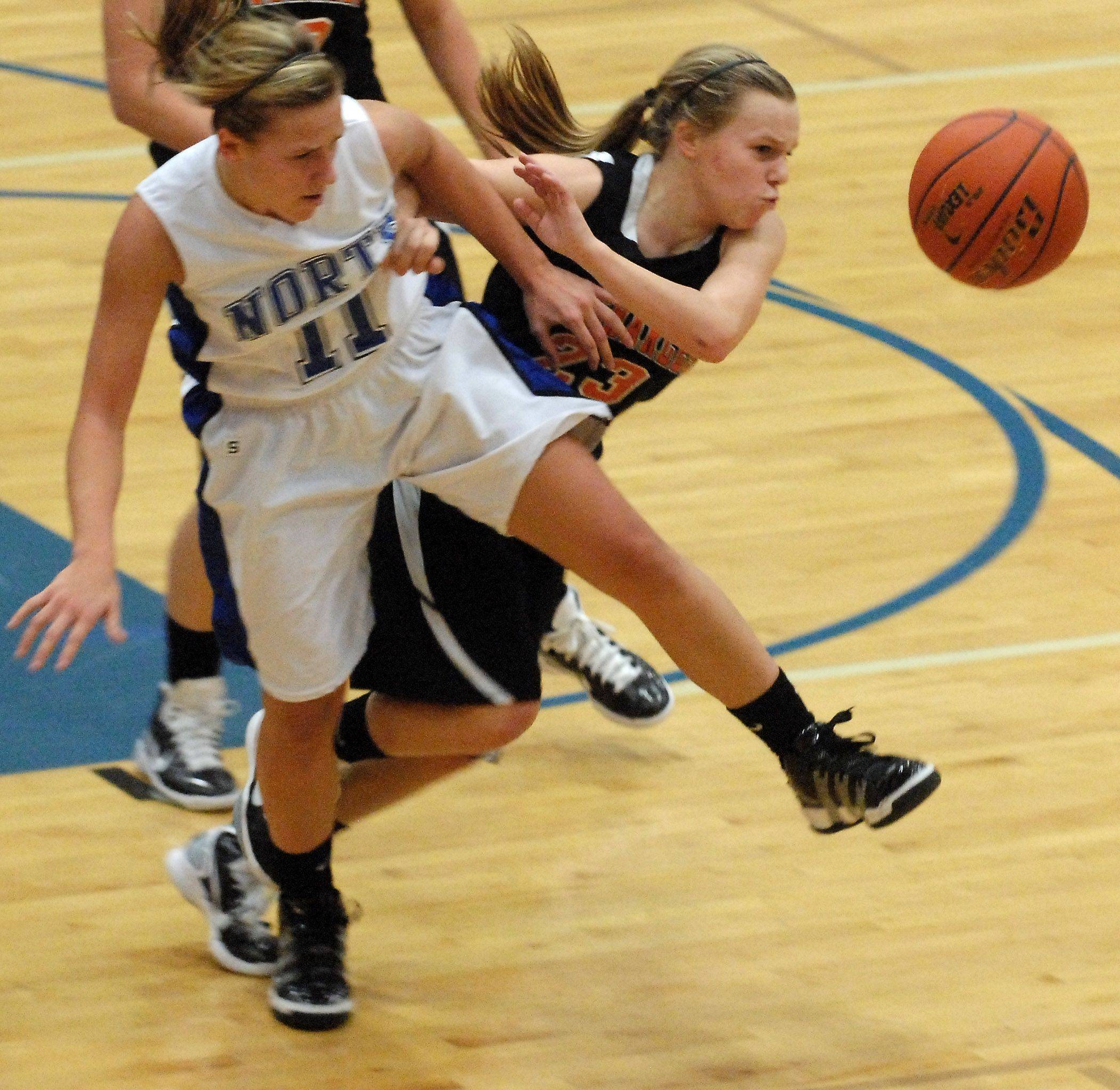 St. Charles North guard Megan Booe and St. Charles East guard Amanda Hilton scramble for a loose ball .