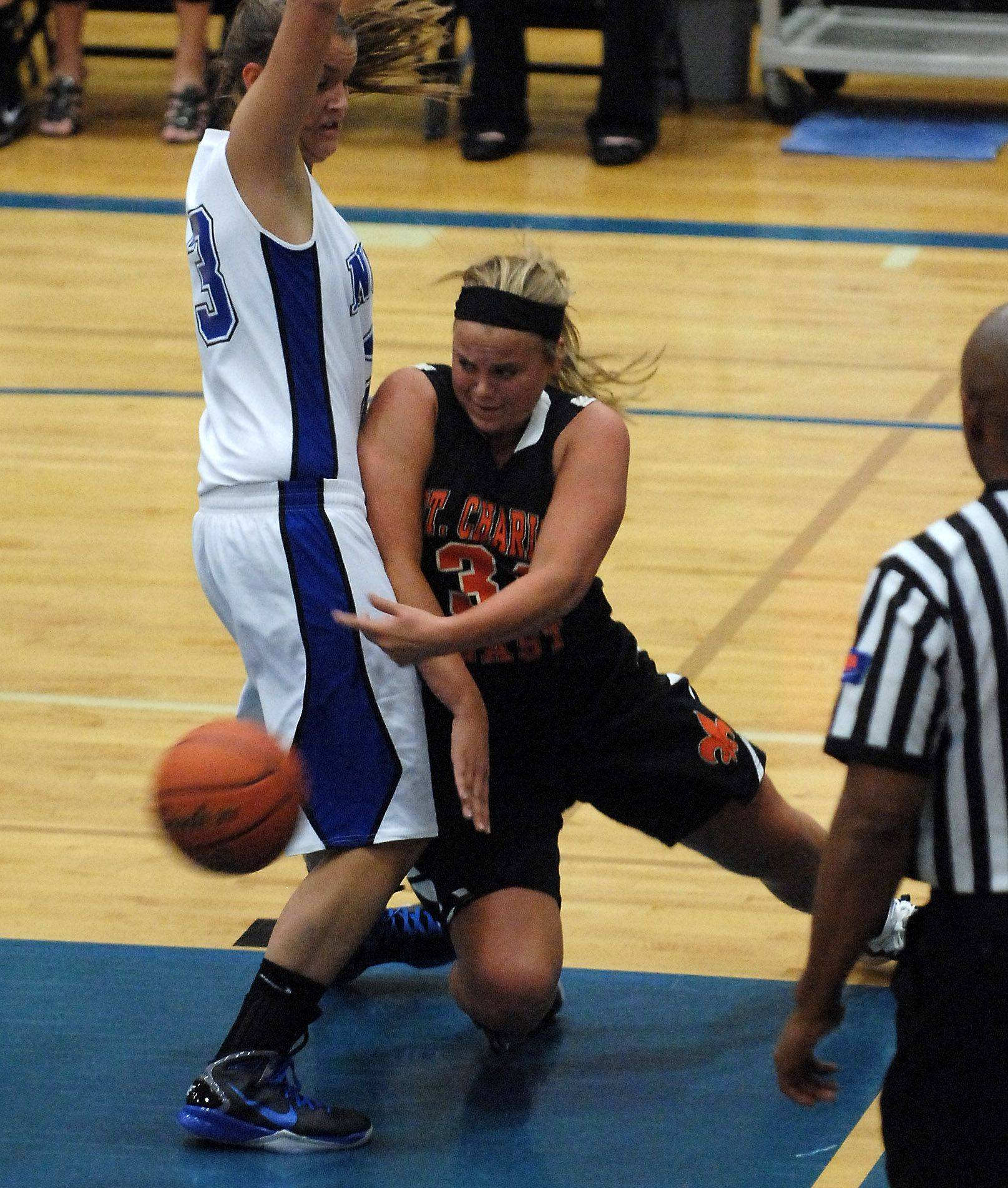St. Charles East forward Morgan Vyzral passes out of a tight spot around St. Charles North's Taylor Russell .