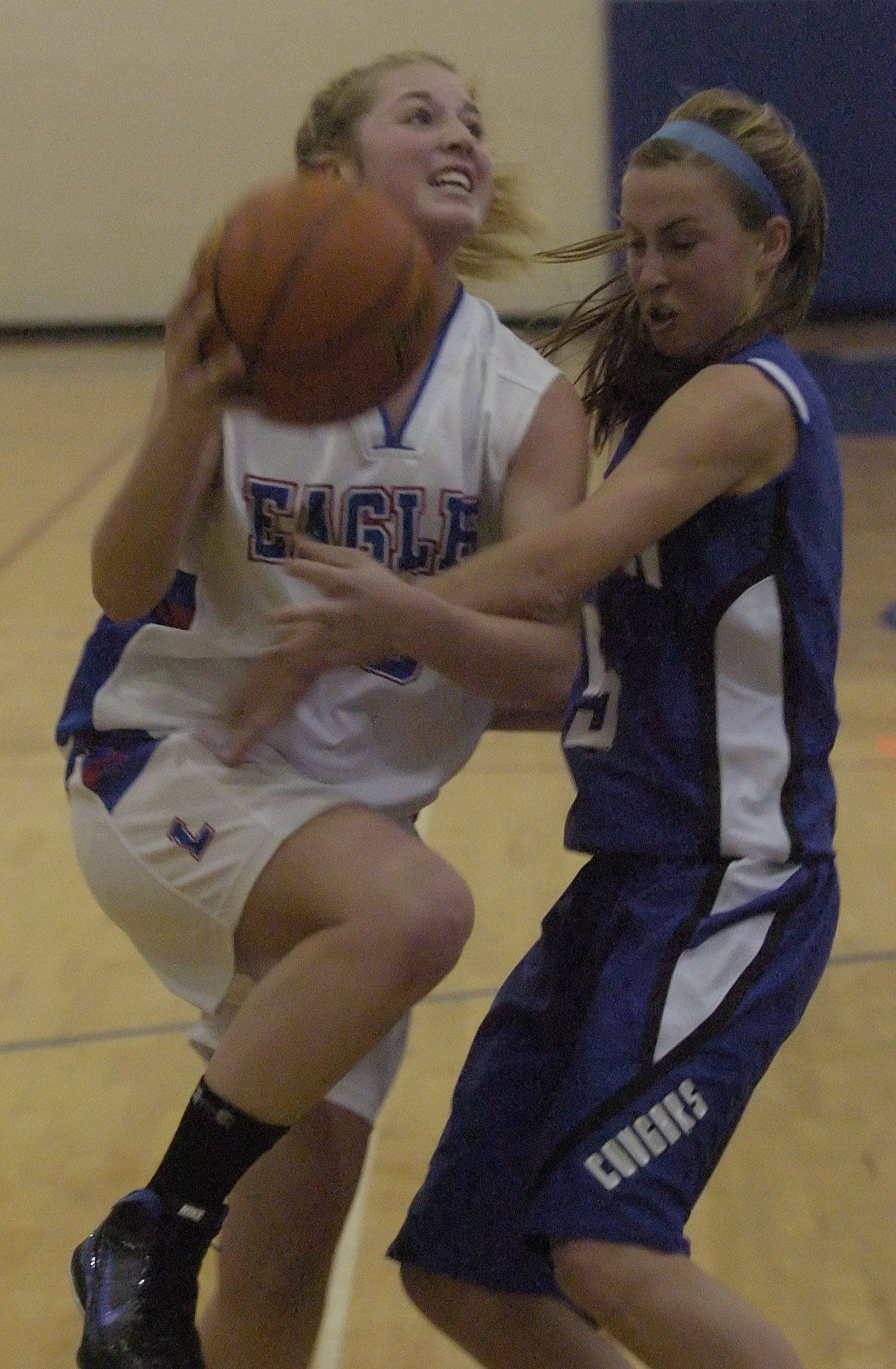 Lakes' Katie Brisner tries to drive past Julie Pecht of Vernon Hills during Saturday's game in Lake Villa.