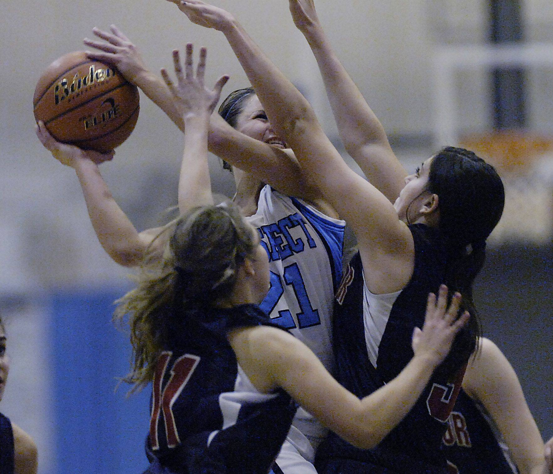 Prospect's Sarah Winans goes up against St. Viator's defense of Julia Frank and Lauren Rooney .
