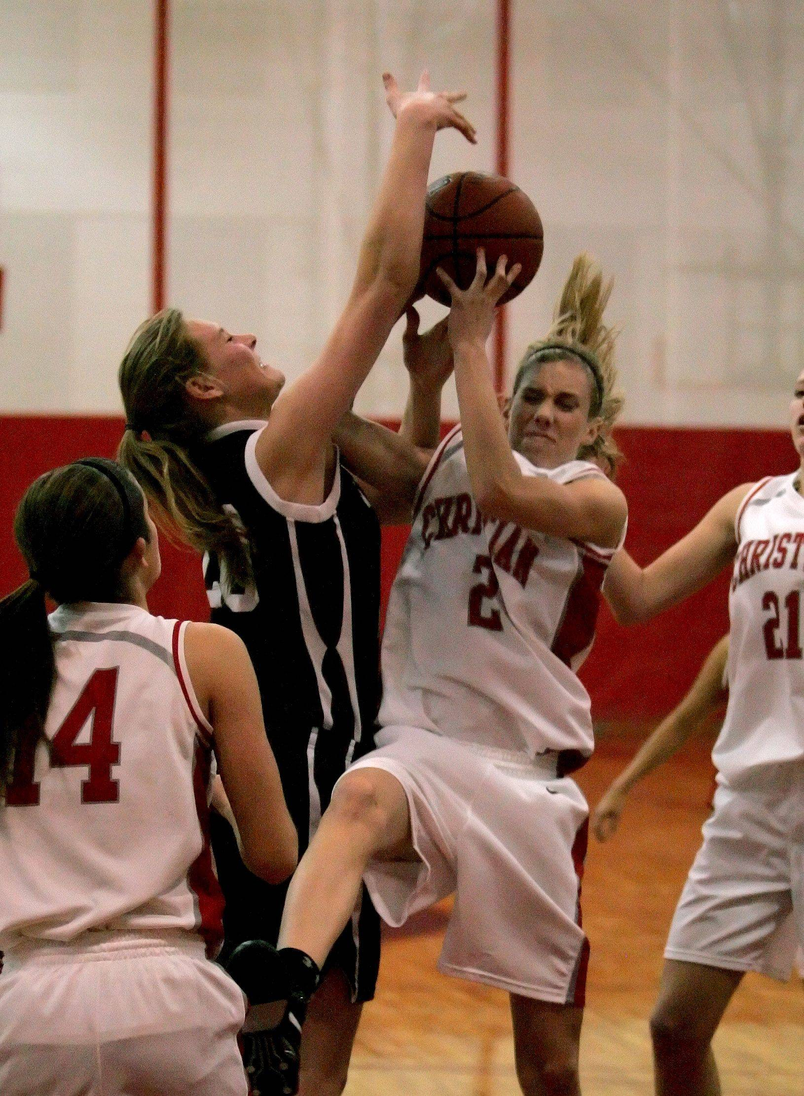 Sarah Drury of Wheaton Academy, left, prevents Mackenzie Bollinger, right of Aurora Christian, from making a shot.