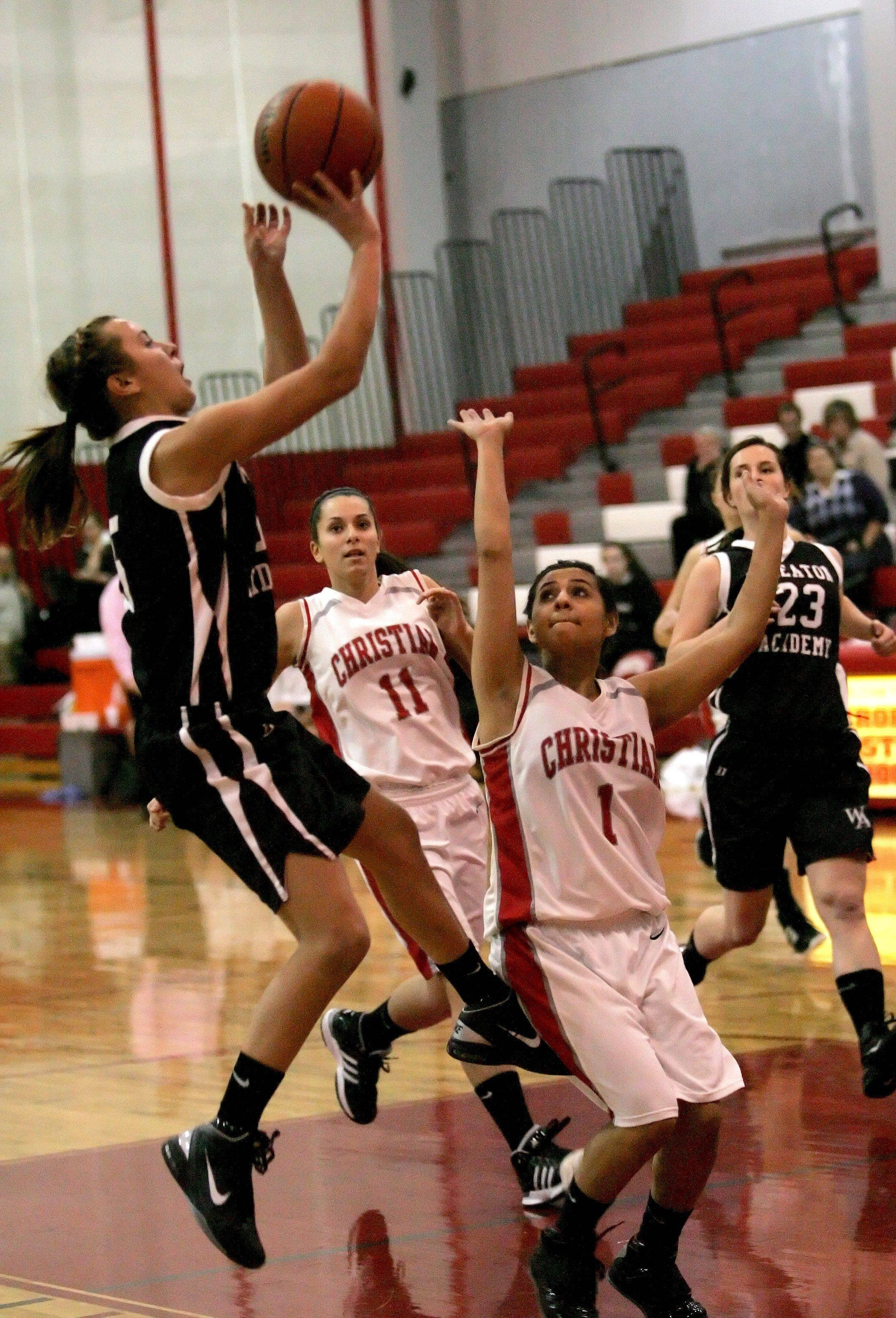Allison Witt of Wheaton Academy, left, makes a shot over Yvette Lira of Aurora Christian .