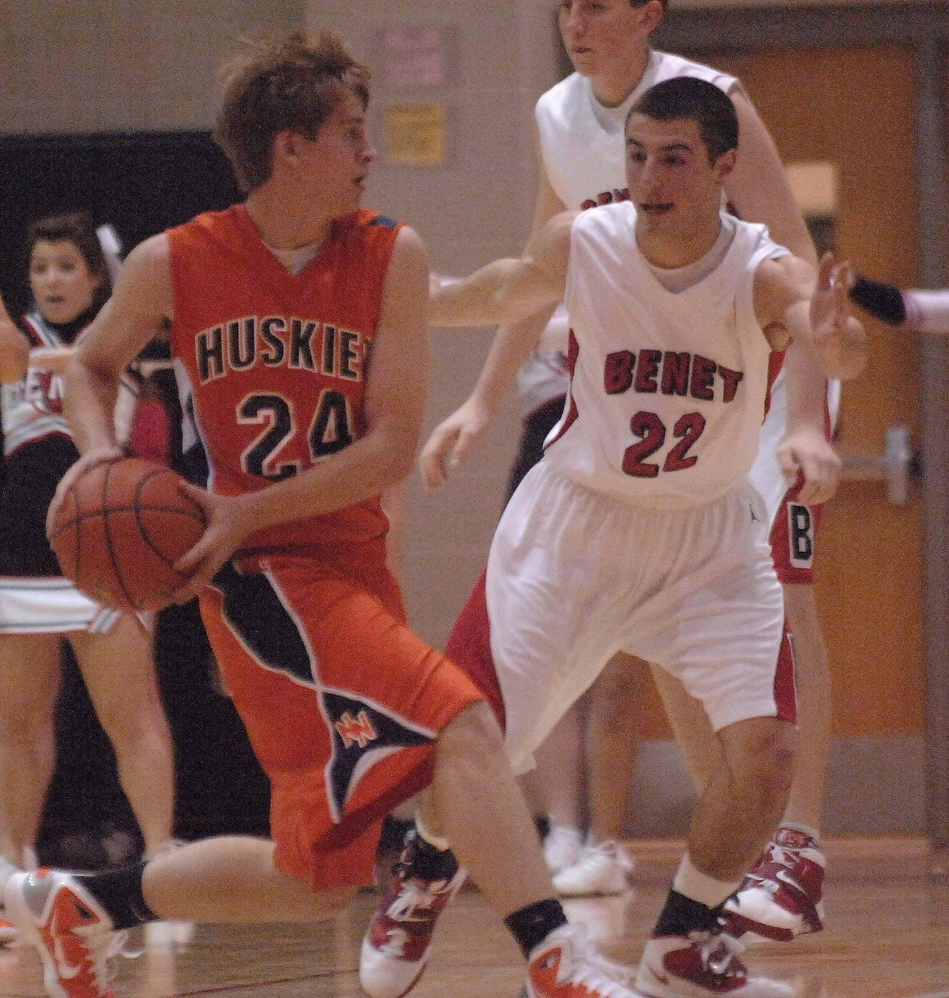 PAUL MICHNA/Pmichna@dailyherald.com Kyle Lindberg of Naperville North looks to pass around Matt Parisi of Benet. This took place during the Naperville North vs. Benet boys basketball game in Lisle Tuesday.