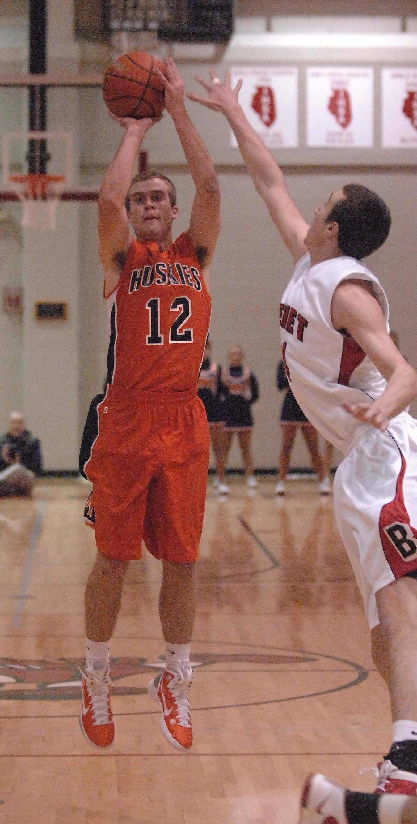 Nick Buege of Naperville North puts up a shot against Benet.