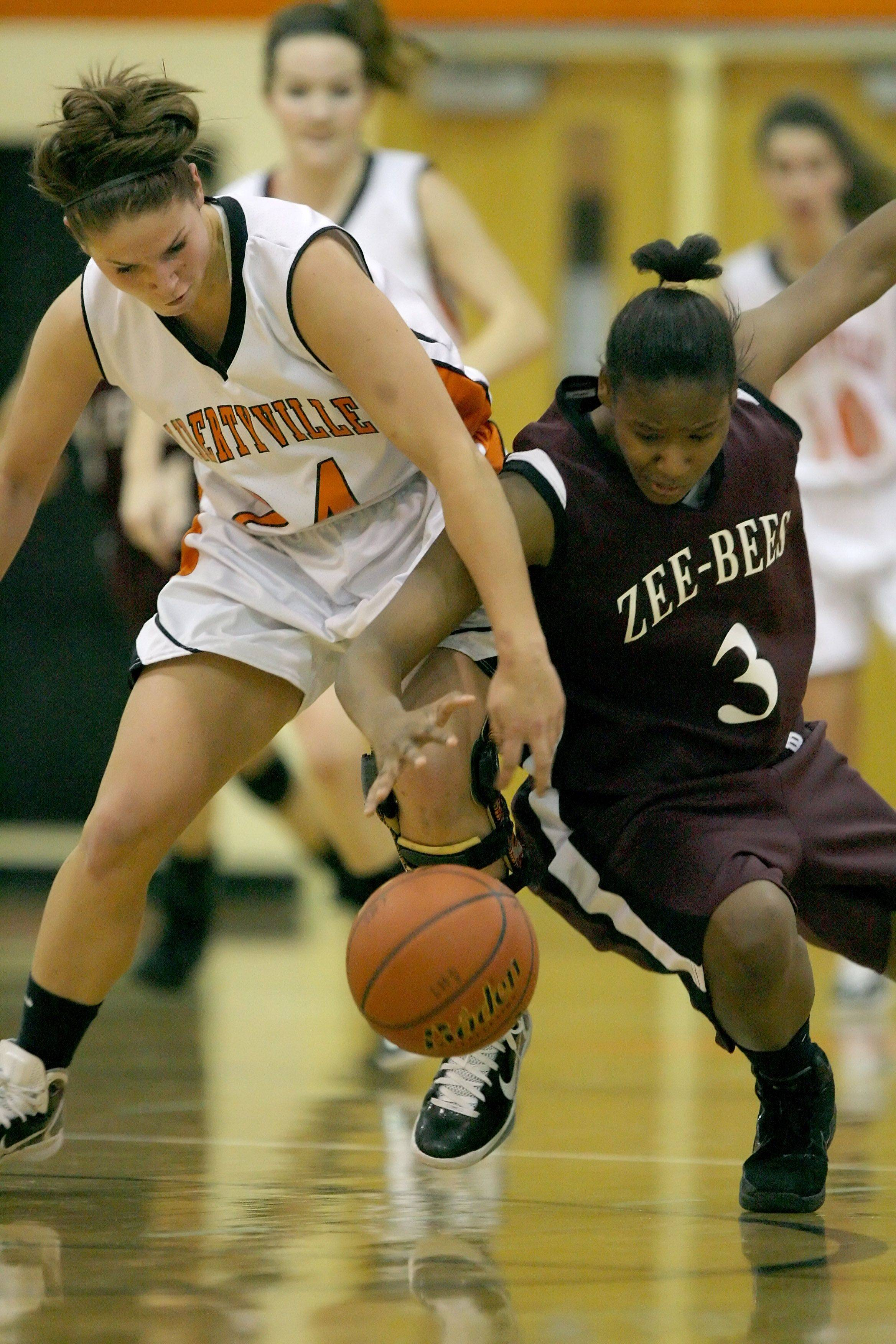 Libertyville's Kaca Savatic, left, and Zion's Octavia Crump battle for a loose ball.