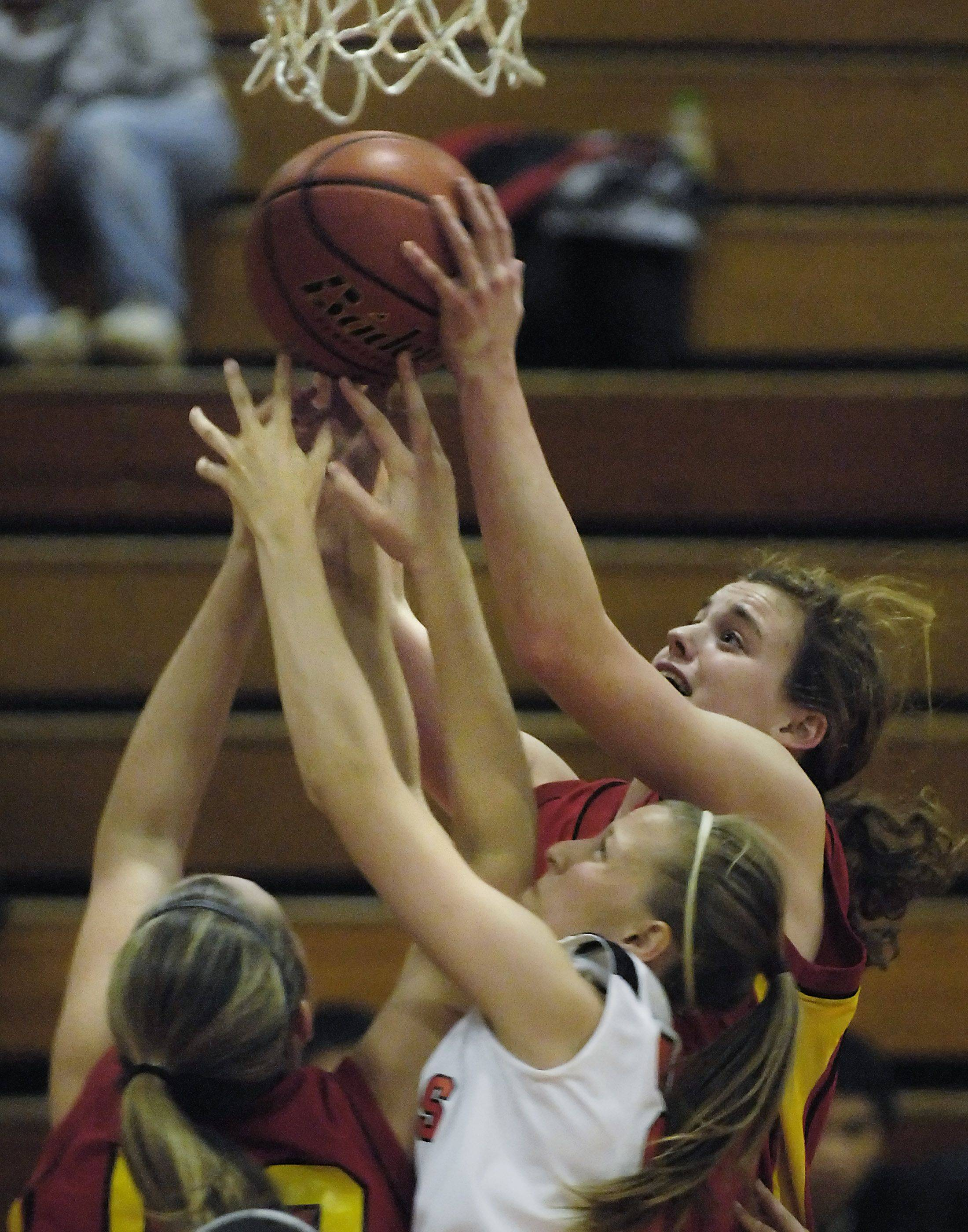 Batavia's Maddie Sychta outstretches teammate Erin Bayram and St. Charles East's Amanda Hilton for a rebound .