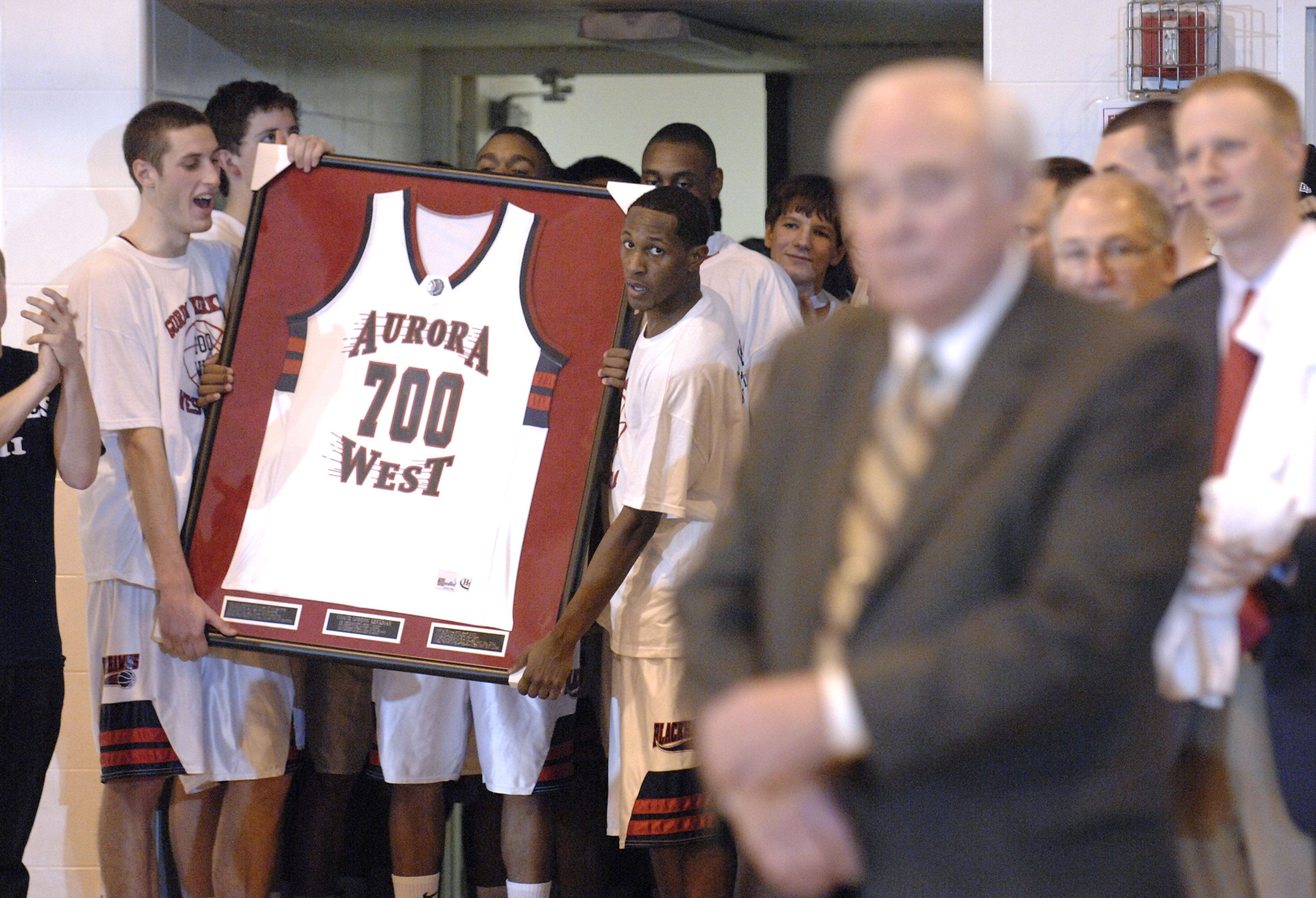 West Aurora coach Gordon Kerkman listens to a presentation after his 700th win at the school while the team waits in the background to present him with a special 700 jersey on Friday, December 10.