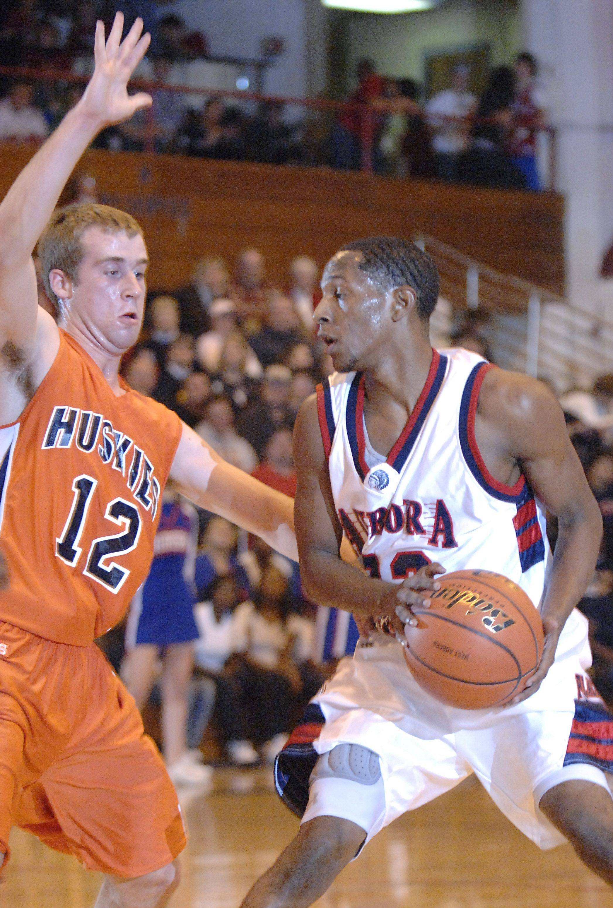 West Aurora's Brandon Hayes pivots around Naperville North's Nick Buege's block in the first half.
