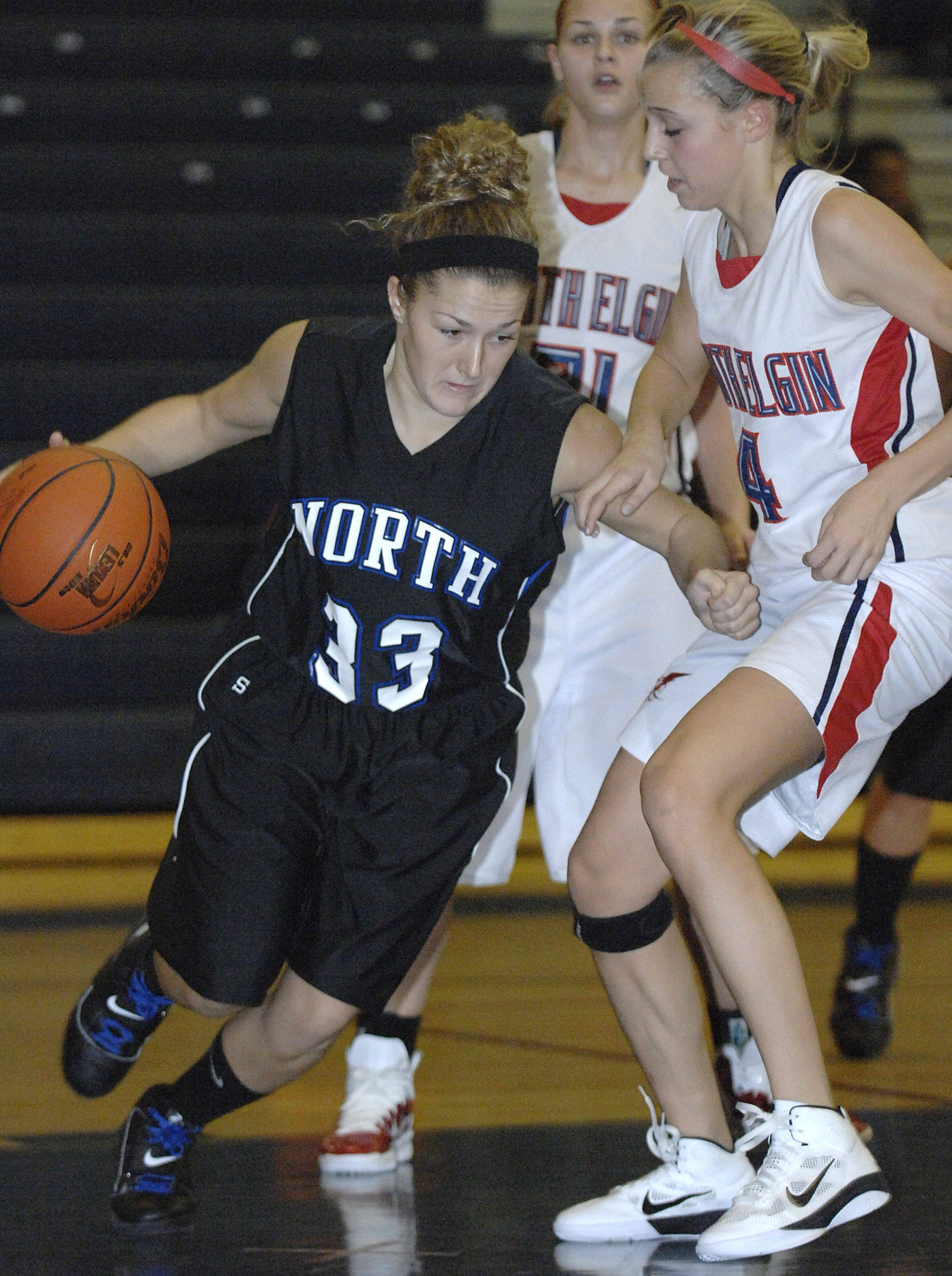Laura Stoecker/lstoecker@dailyherald.com South Elgin's St. Charles North's Taylor Russell drives around South Elgin's Savanah Uveges in the second quarter on Saturday, December 11.