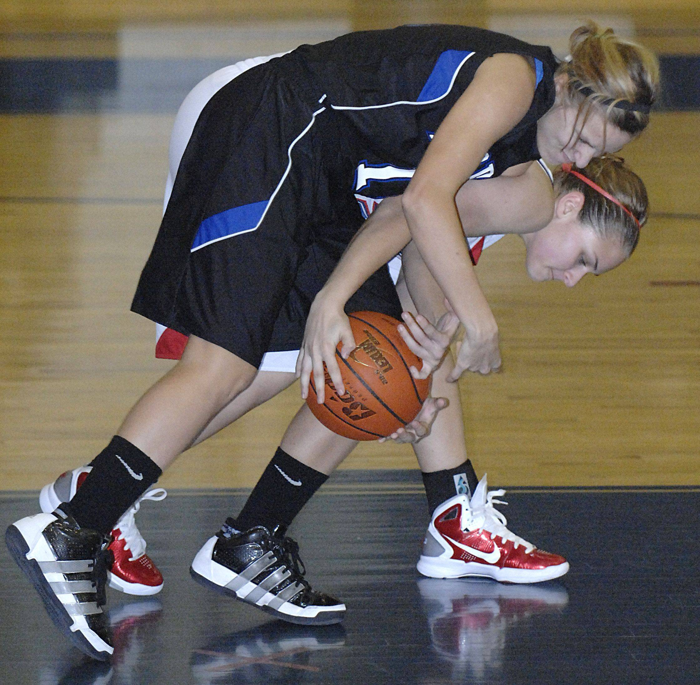 Laura Stoecker/lstoecker@dailyherald.com St. Charles North's Megan Booe and South Elgin's Amanda Behles wrestle for the ball near the Storm's hoop in the second quarter on Saturday, December 11.