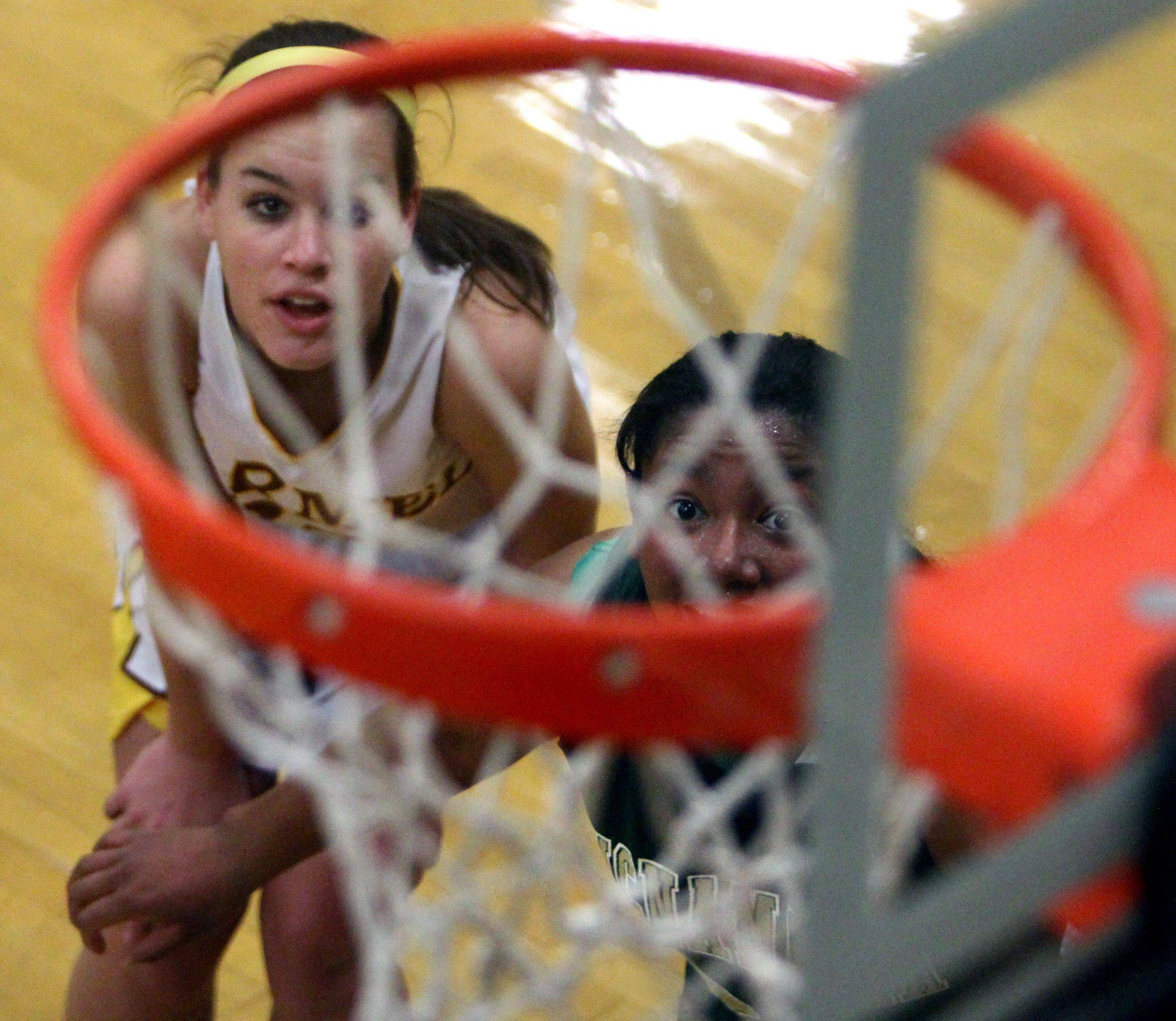 George LeClaire/gleclaire@dailyherald.com Carmel's Kaitlyn Lynch eyes the net during a free-throw shot with Bishop McNamara defender Erika Tatum in Mundelein on Saturday, December 11.