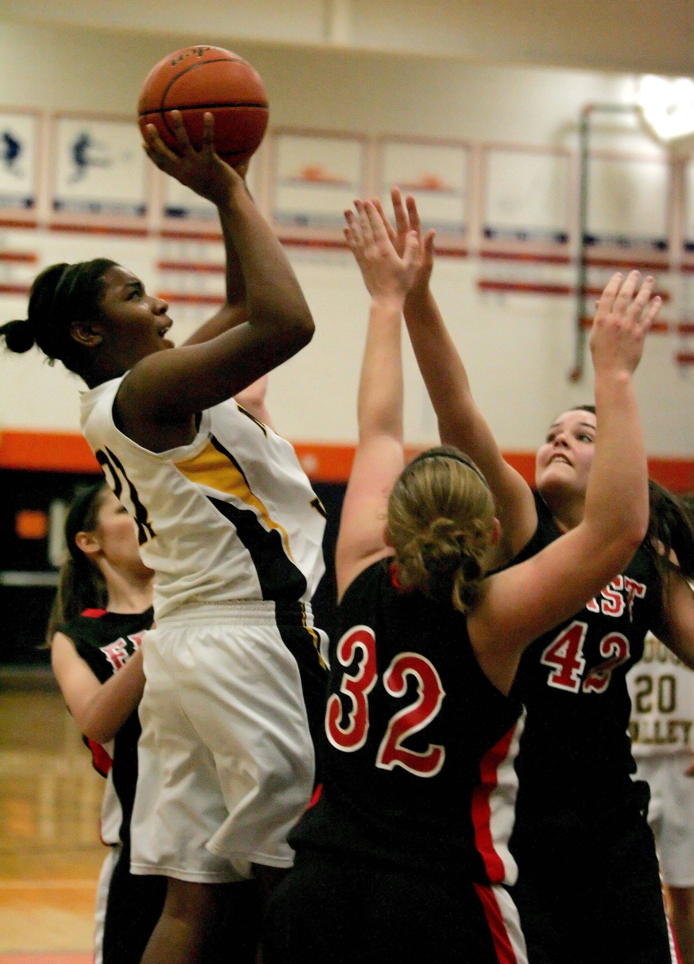 Amber Smith of Neuqua Valley, left, takes a shot over Megan Shannon, center, and Sarah Moylan, right of Glenbard East.