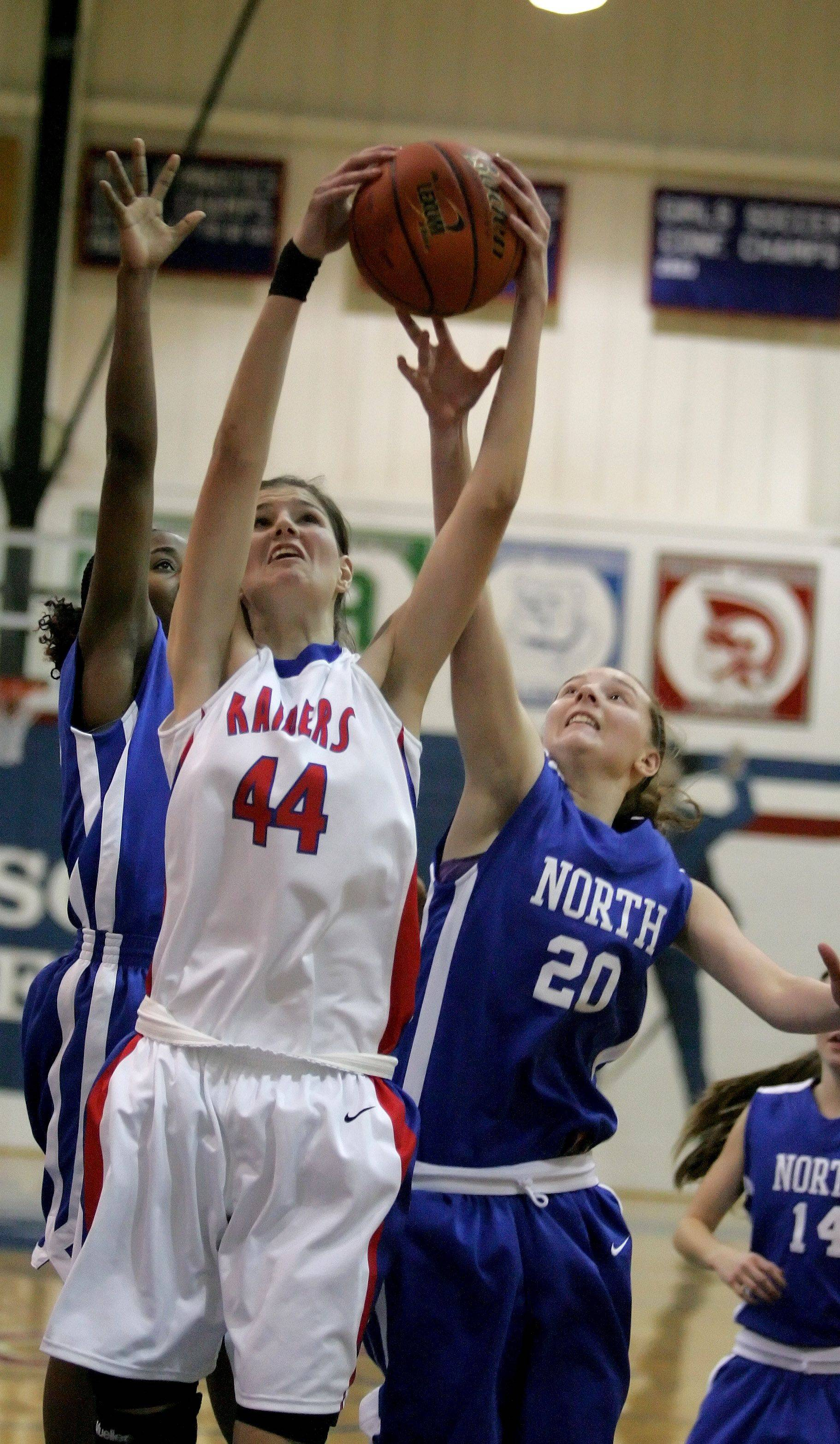 Nevena Markovic, left, of Glenbard South and Maddie Baillie, right, of Wheaton North go up for the rebound in girls basketball action Tuesday in Glen Ellyn.