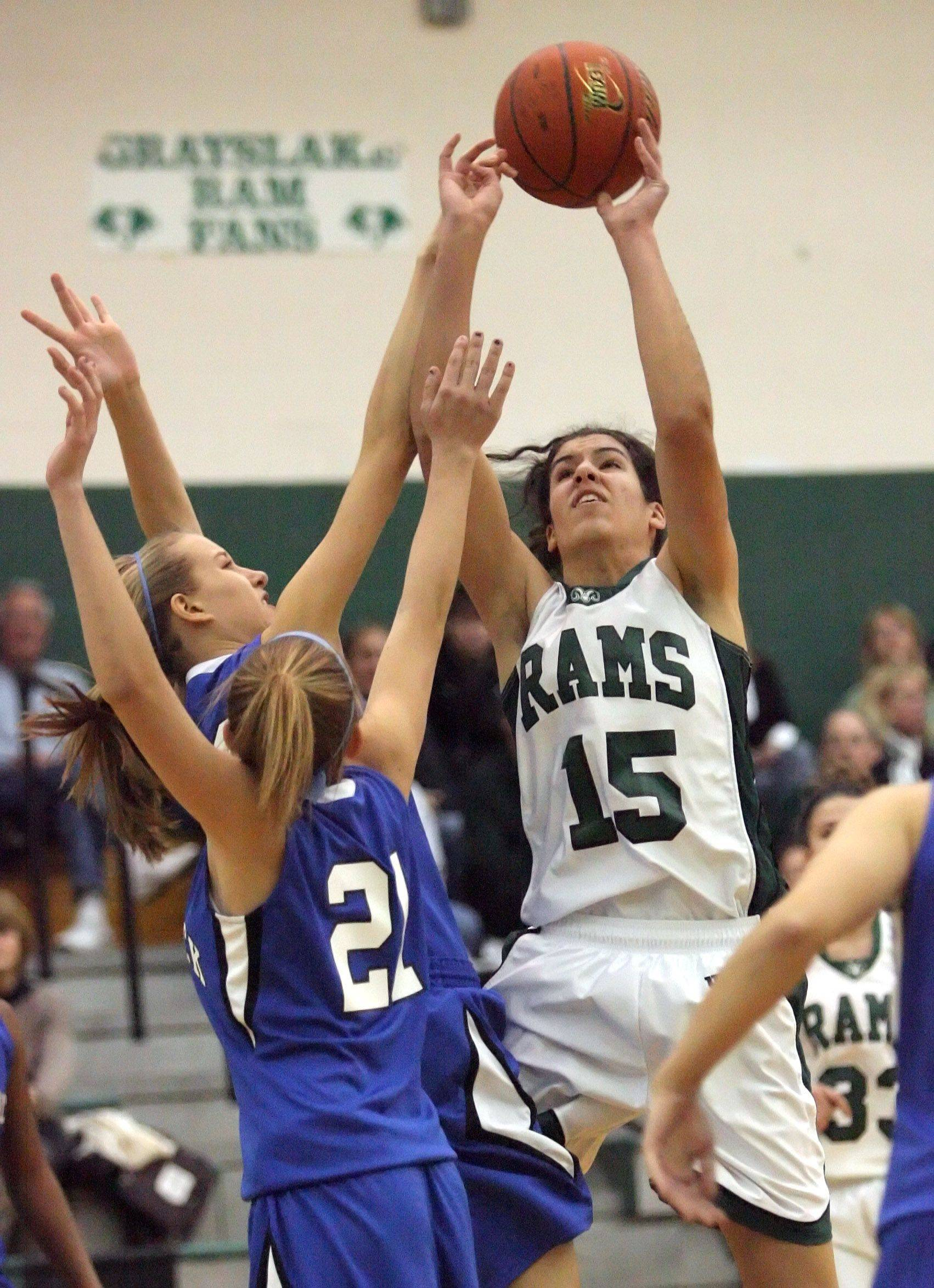 Grayslake Central's Rebekah Llorens shoots over Woodstock's Cody Brand, left, and Sami Ludwig .