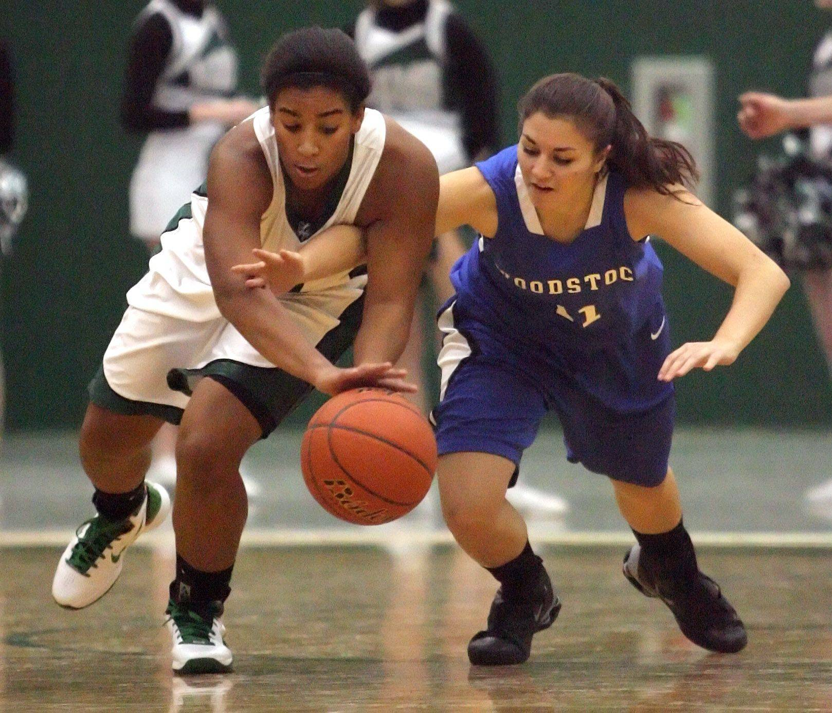 Grayslake Central's Alex Scarbro, left and Woodstock's Odessa Peters scramble for a loose ball .