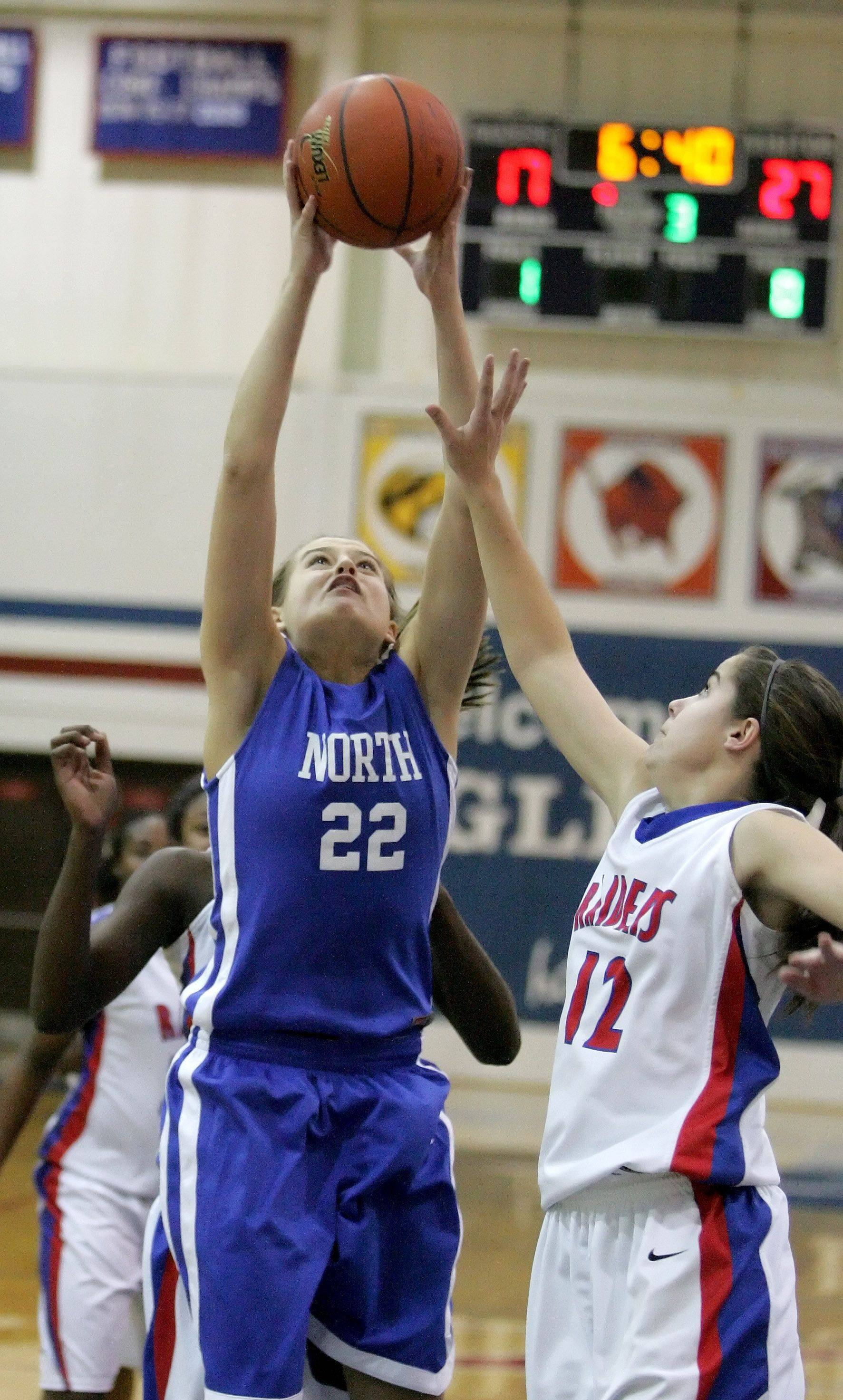 A.K. Feltes of Wheaton North goes up for a basket as Alyse Cates of Glenbard South, right, defends.