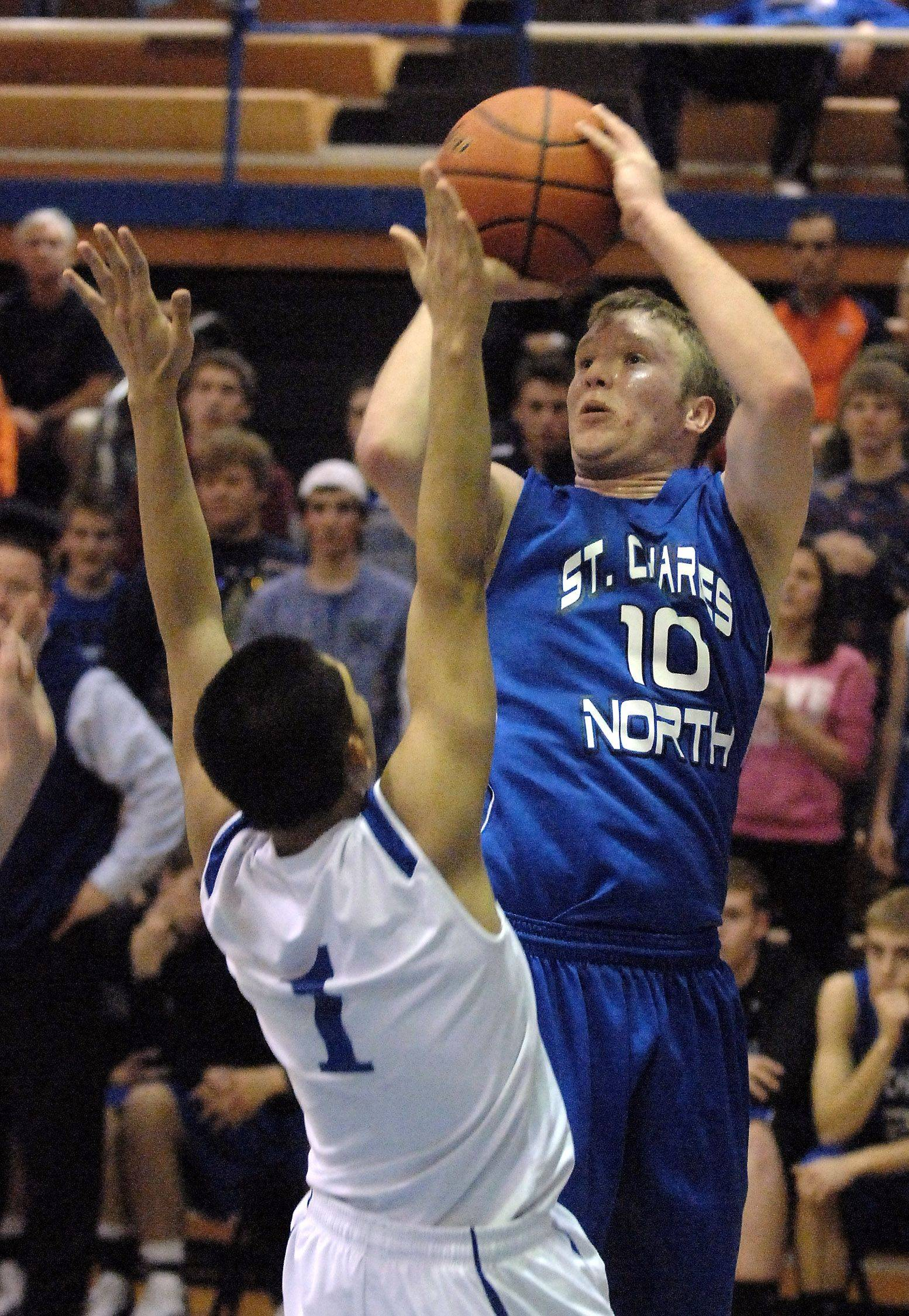 St. Charles North's Chris Conrad shoots a jumper over Vincent Sarangaya.