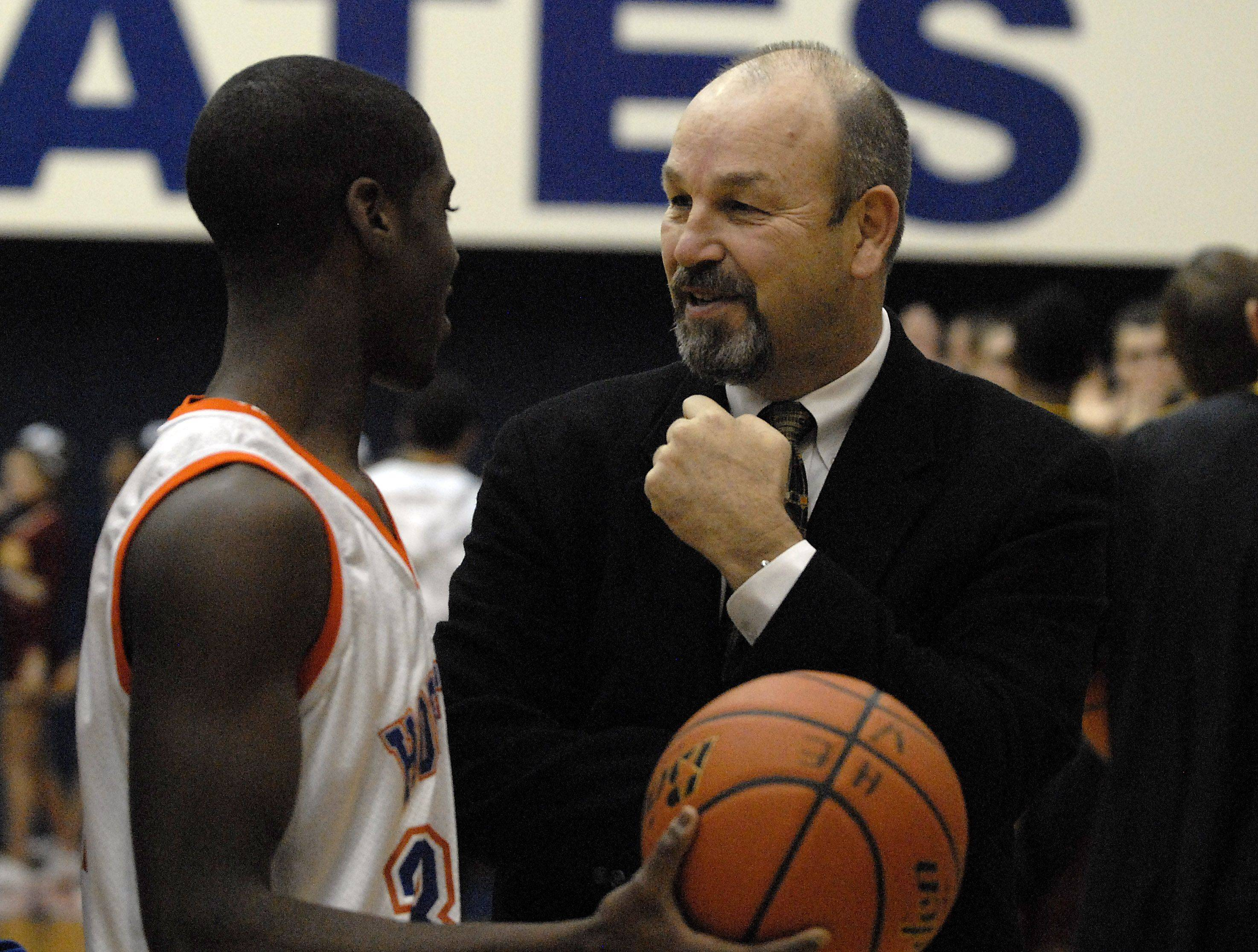 Hoffman Estates boys basketball head coach Bill Wandro talks to his player, Austin Terry, before the game .
