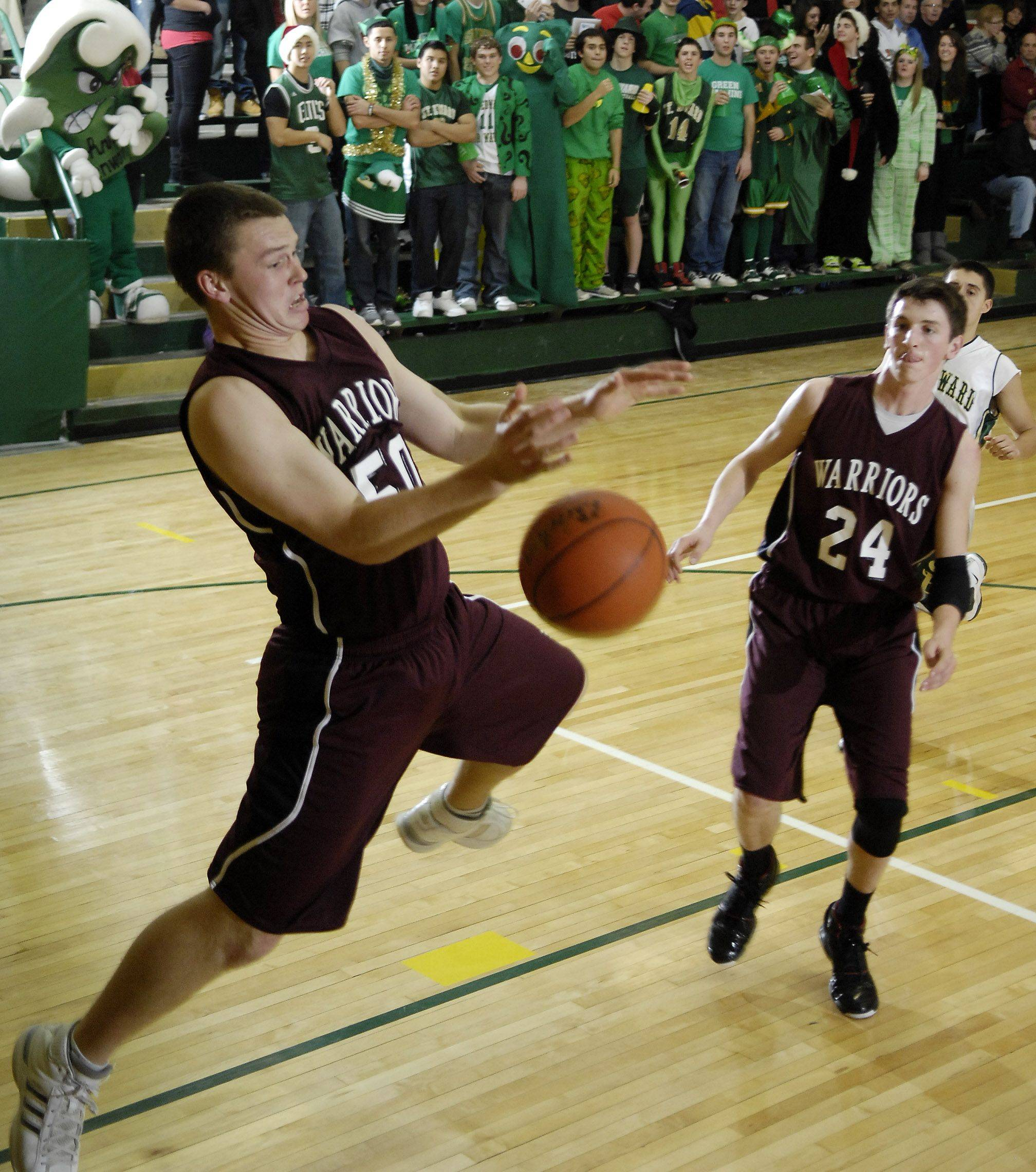 Wheaton Academy's Tate Fritz grabs a rebound during Friday's game at St. Edward High School in Elgin.