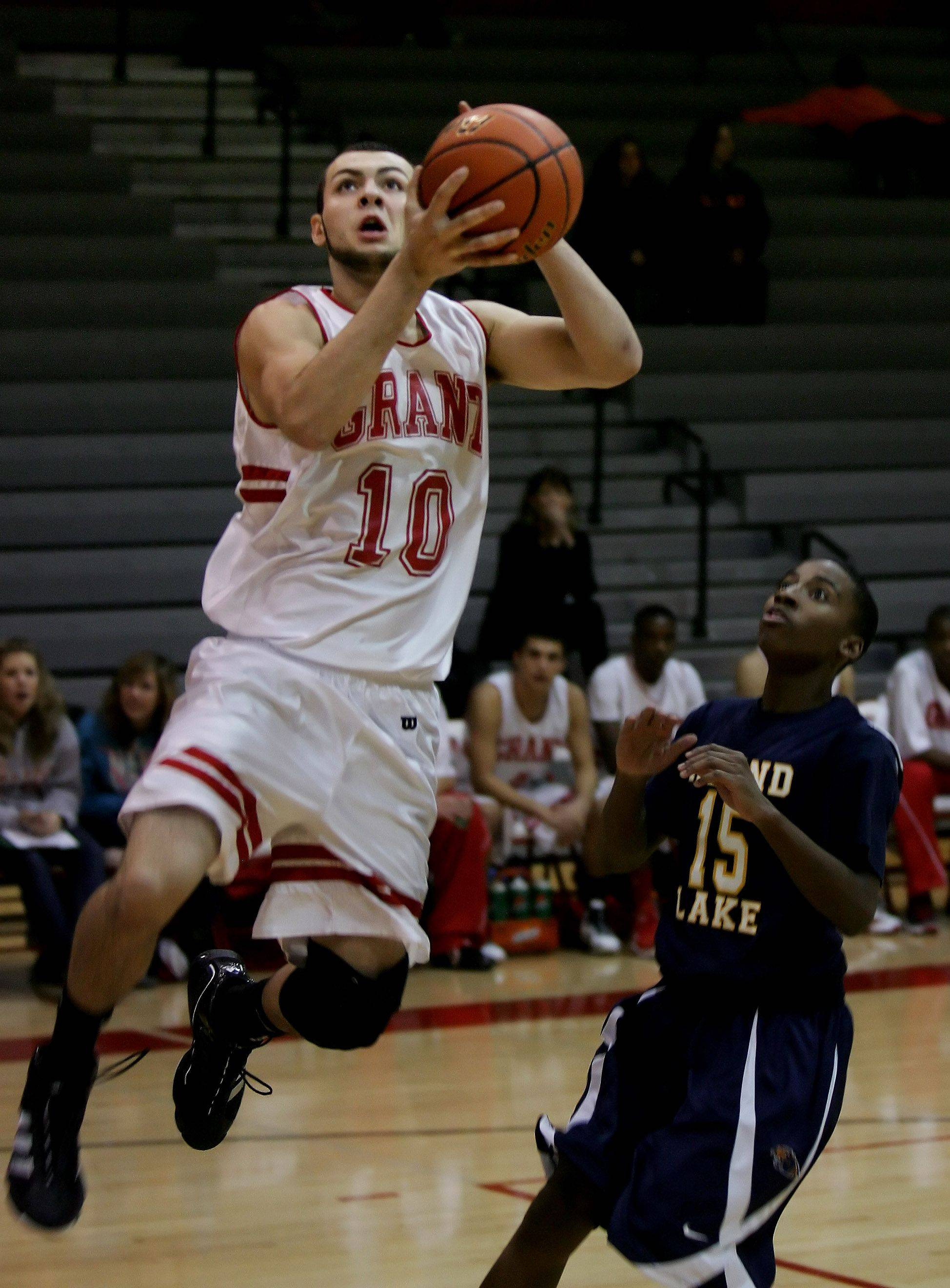 Grant forward Jerry Gaylor drives past Round Lake guard Teandre Brown for a layup.