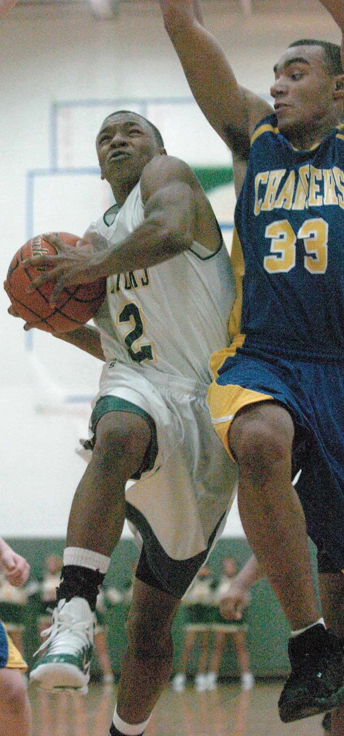 Jakobi Johnson of Waubonsie goes up for a shot around Robert DeMyers of Aurora Central.
