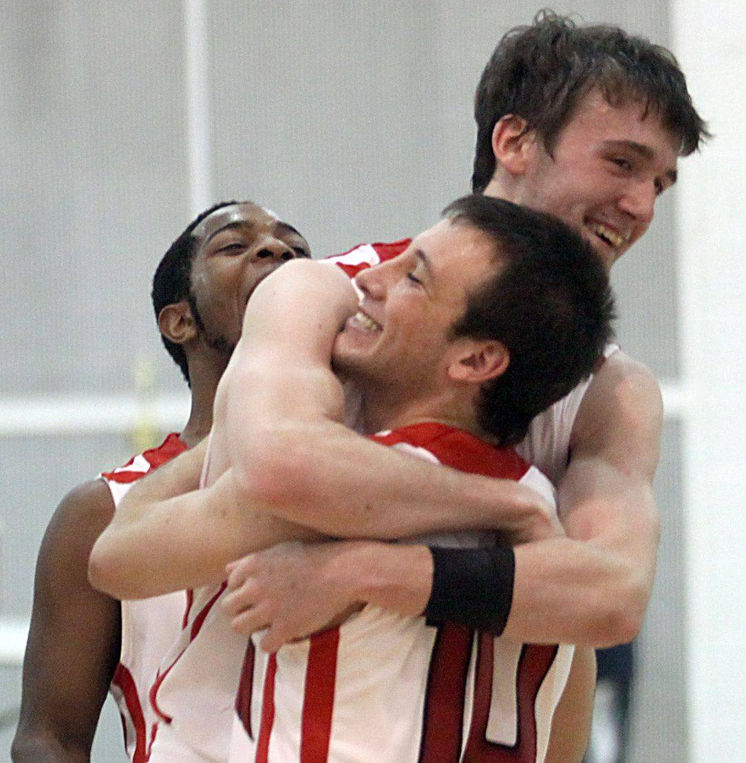 From left, Leavon Head, Ryan Sawvell, and Charlie Gandolfi of Mundelein celebrate victory after the title game of the Jacobs Holiday Classic Boys Basketball Tournament in Algonquin.