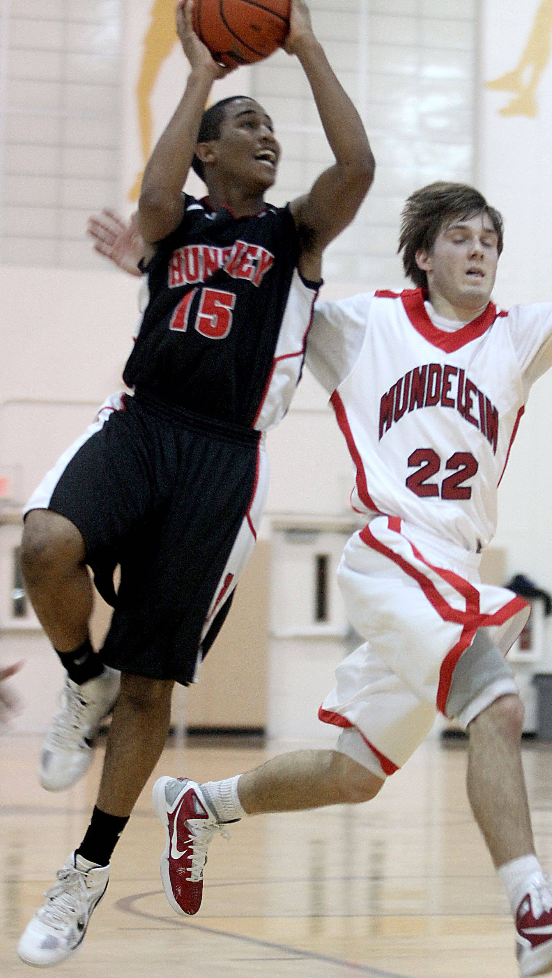 Bryce Only of Huntley, left, shoots past the defense of Robert Knar of Mundelein during the title game of the Jacobs Holiday Classic Boys Basketball Tournament in Algonquin on Thursday night.