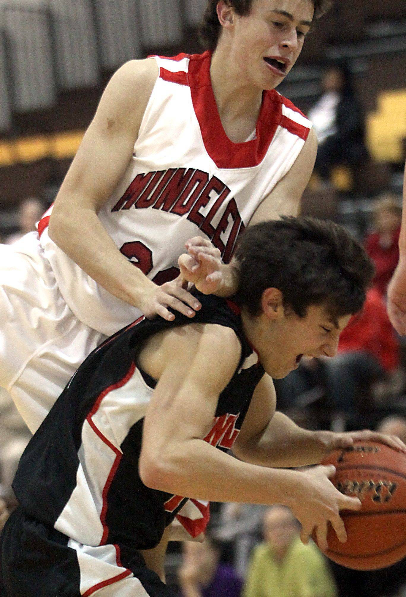 Patrick Kunzer/pkunzer@dailyherald.com Jake Dachman of Huntley, bottom, tries to keep a handle on the basketball as Nate Brune of Mundelein plays defense during the title game of the Jacobs Holiday Classic Boys Basketball Tournament in Algonquin on Thursday night.