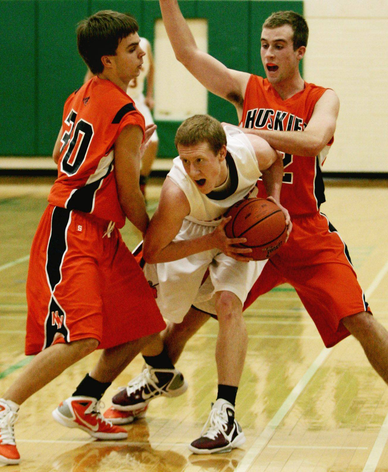 Naperville North's Chris Mullen, left, and Kyle Lindberg, far right, battle Bob Harmening of Brother Rice Monday night at York High School in Elmhurst.