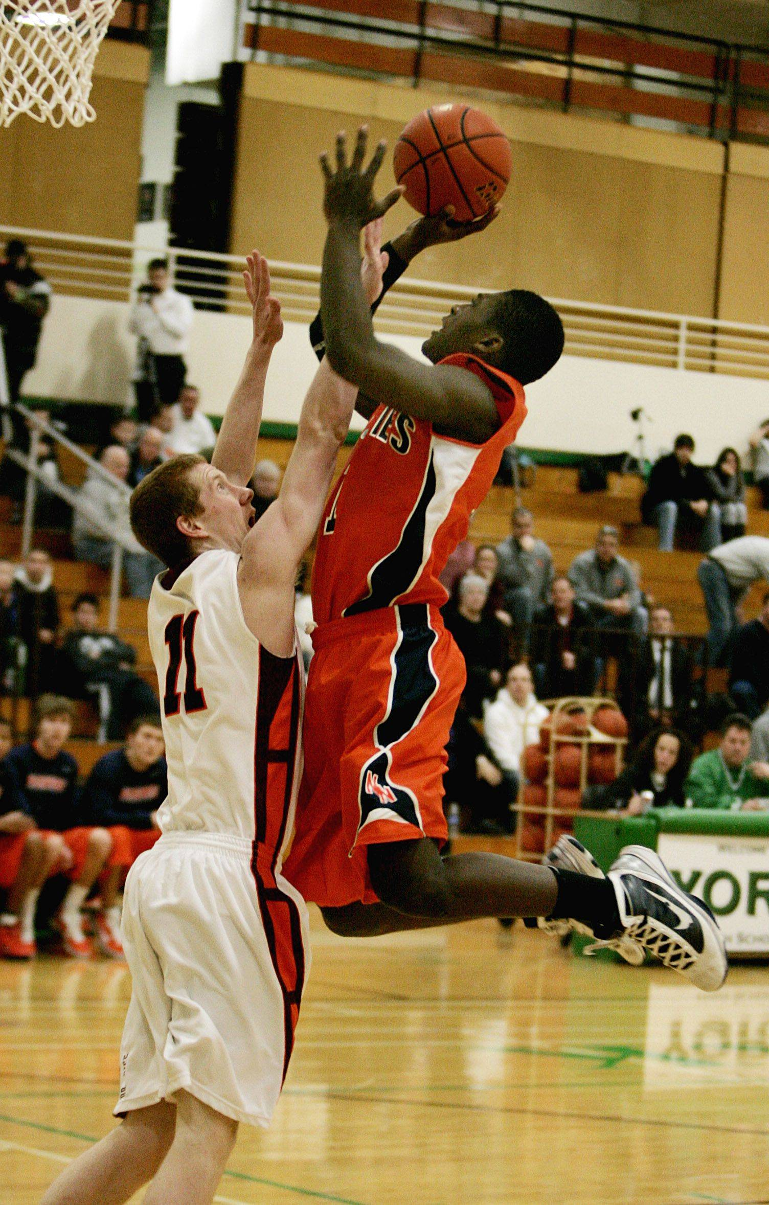 Naperville North's Jovonn Griffin, right, goes up for the basket against Brother Rice's Bob Hayes, left, during their game Monday night.
