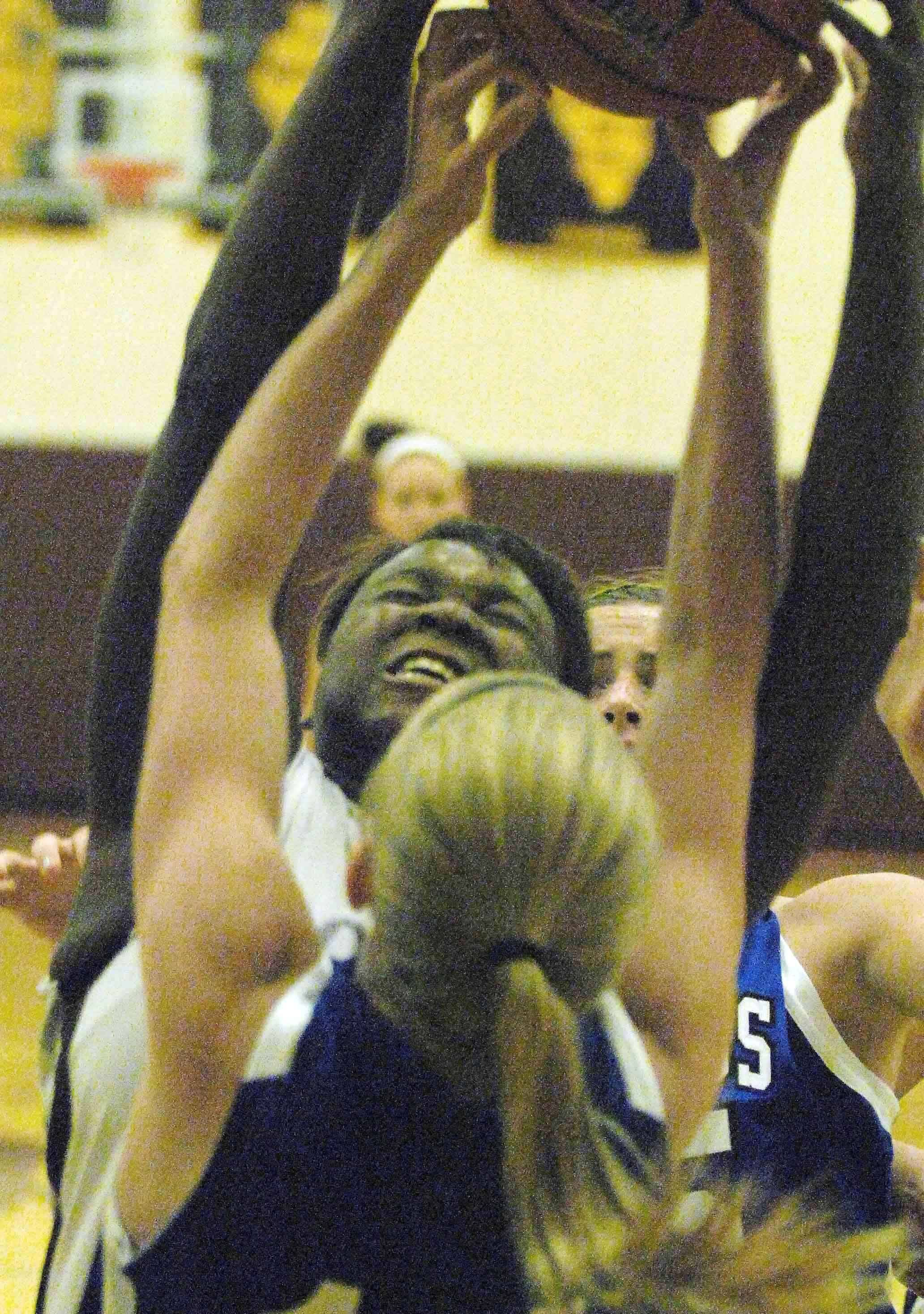 PAUL MICHNA/Pmichna@dailyherald.comTianna Brown of Montini fights off a Columbus defender for a rebound during the Montini vs. Columbus game at Montini Tuesday.