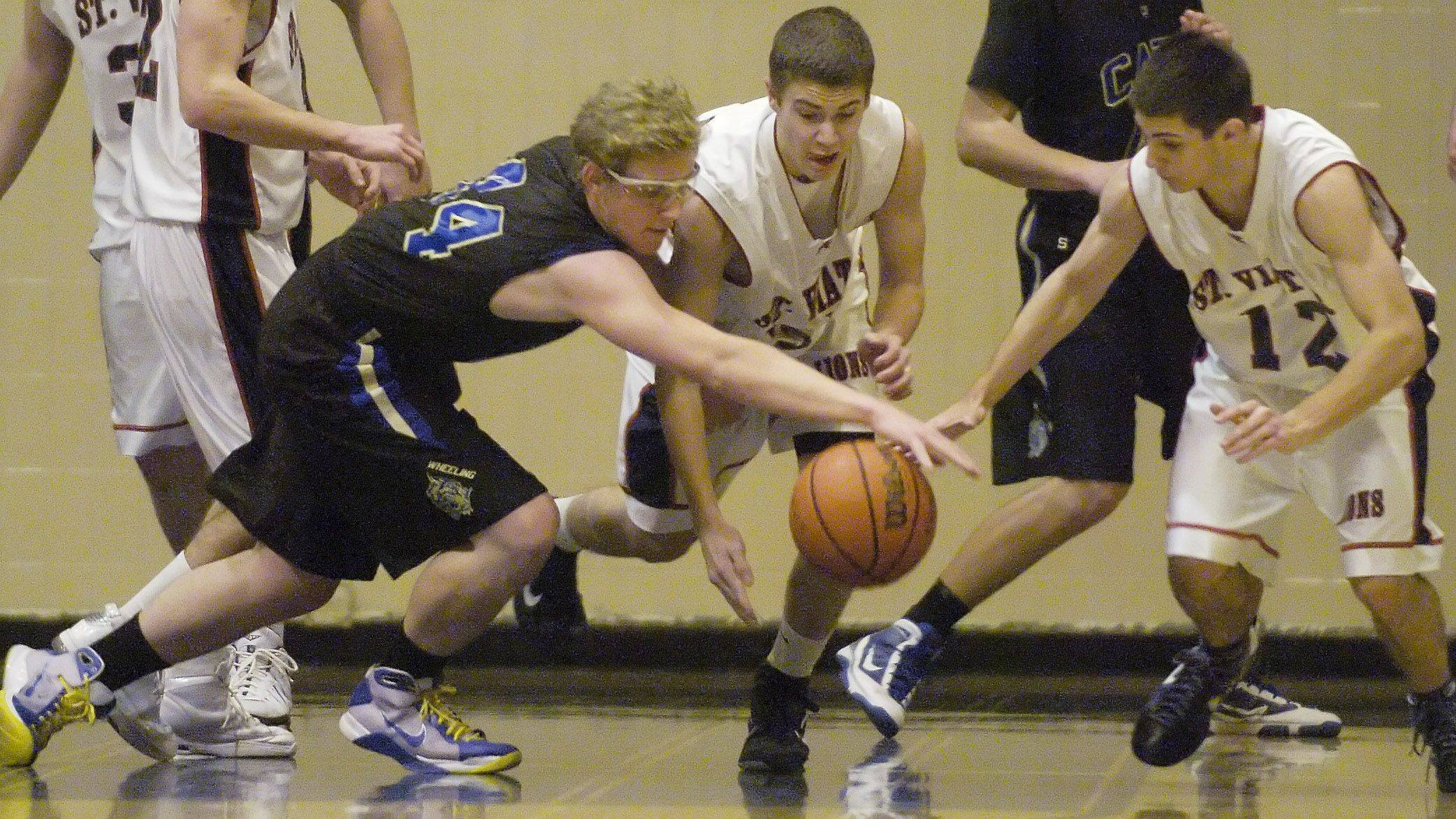 Left to right, Wheeling's Matt Hart and St. Viator's Brian Wilhite and D.J. Morris try to get their hands on a loose ball during the Wheeling Tournament Wednesday.