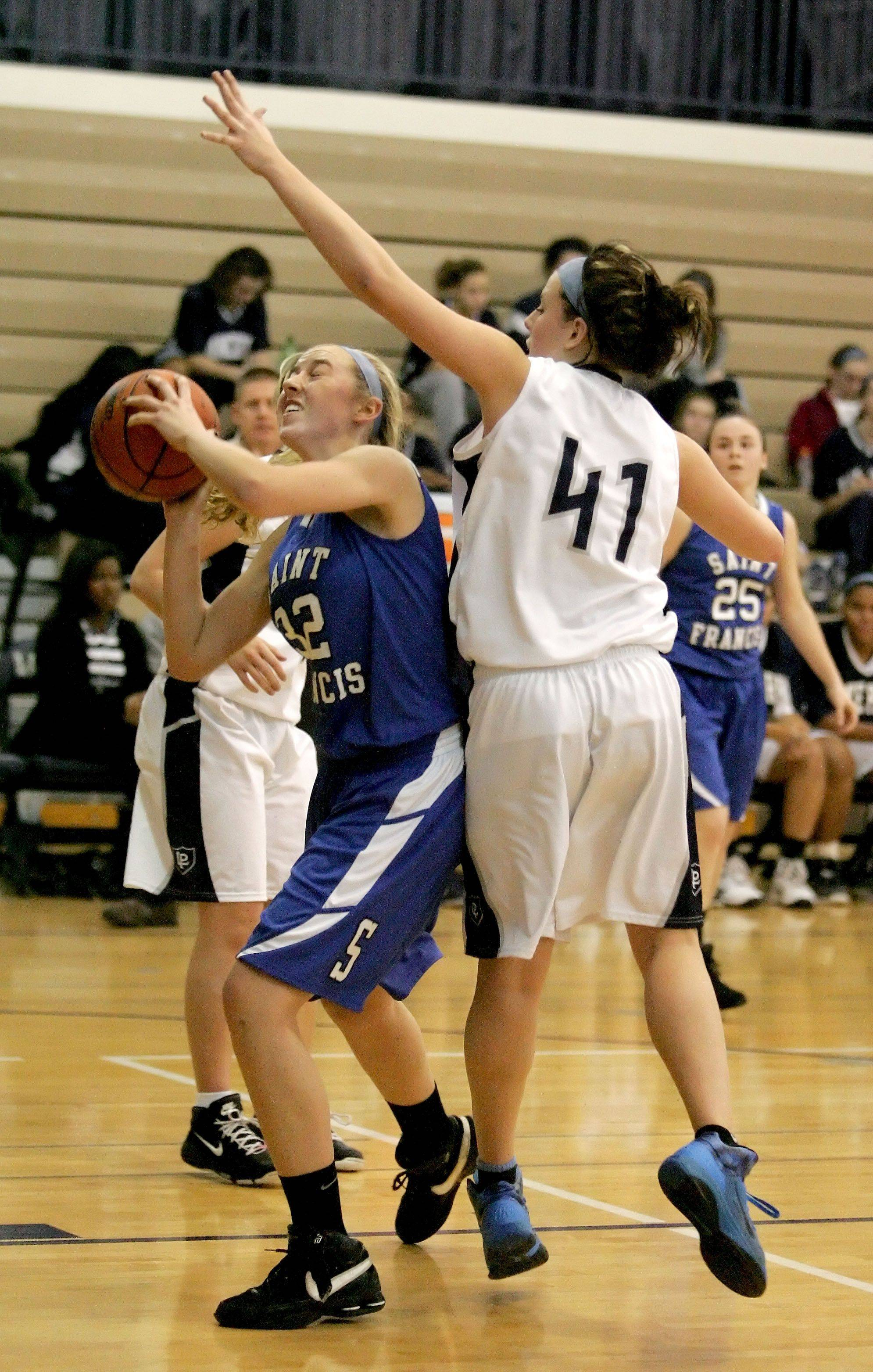 Fiona McMahon of St. Francis, left, takes a shot as Alexis Hahn of Lake Park plays defense.
