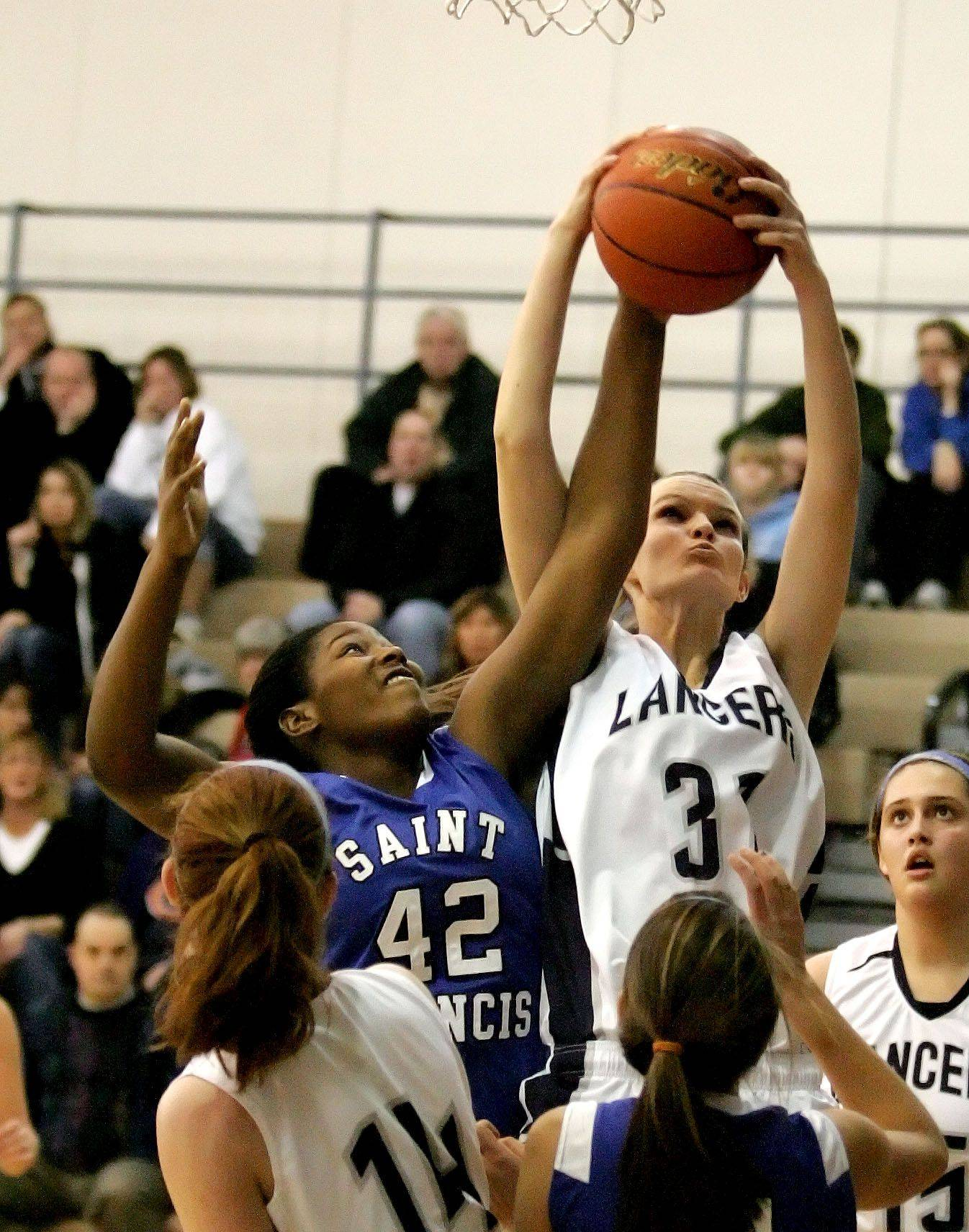 Tia Talley, left of St. Francis and Ashleigh Ricchio, right, of Lake Park go up for a rebound.