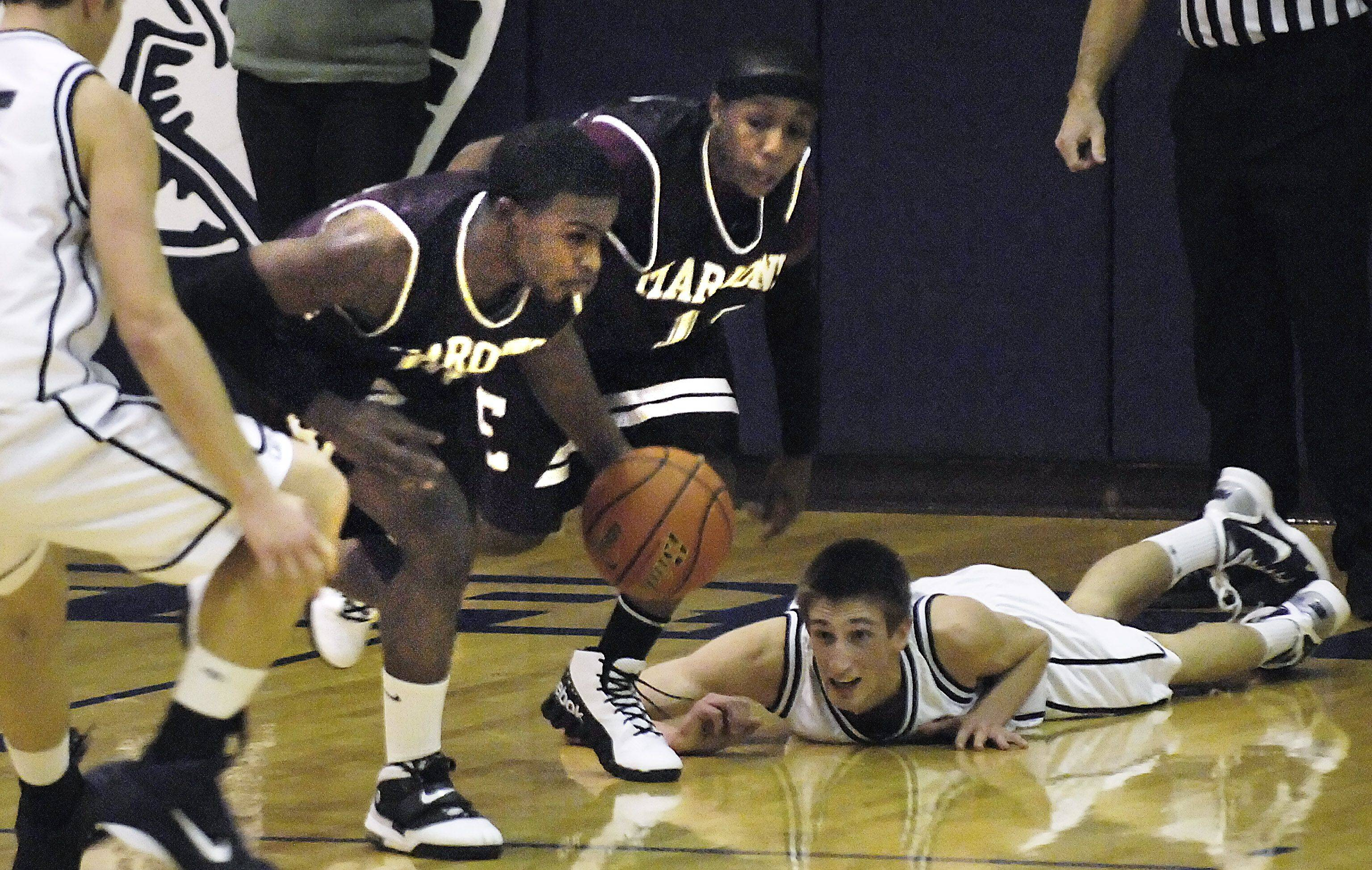 Cary-Grove's Matt Aulert watches from the floor as Elgin's Jordan Dean runs away with a loose ball .
