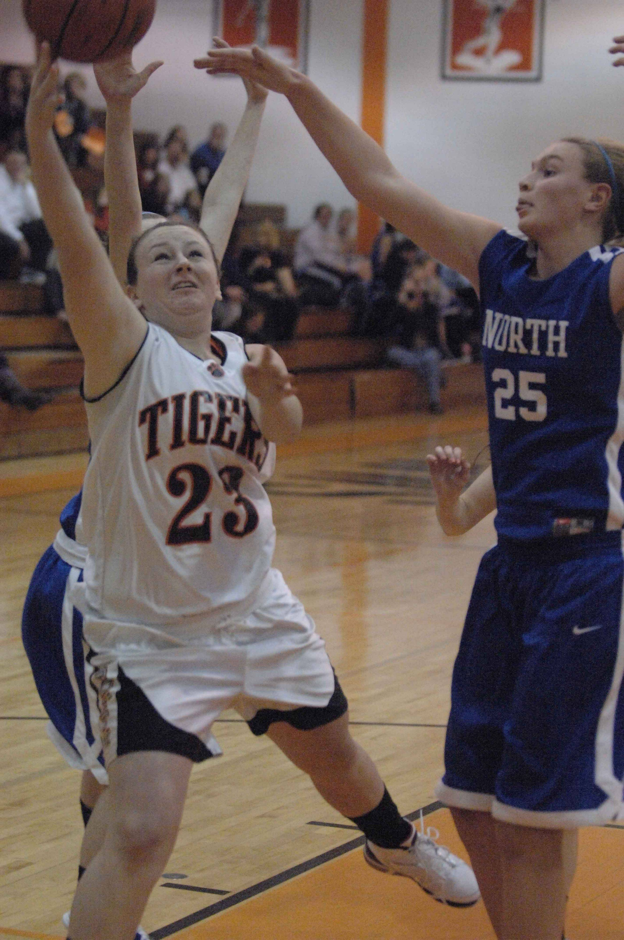 Annie Shain of Wheaton Warrenville South takes a shot while Mandy Traversa of Wheaton North tries to block.
