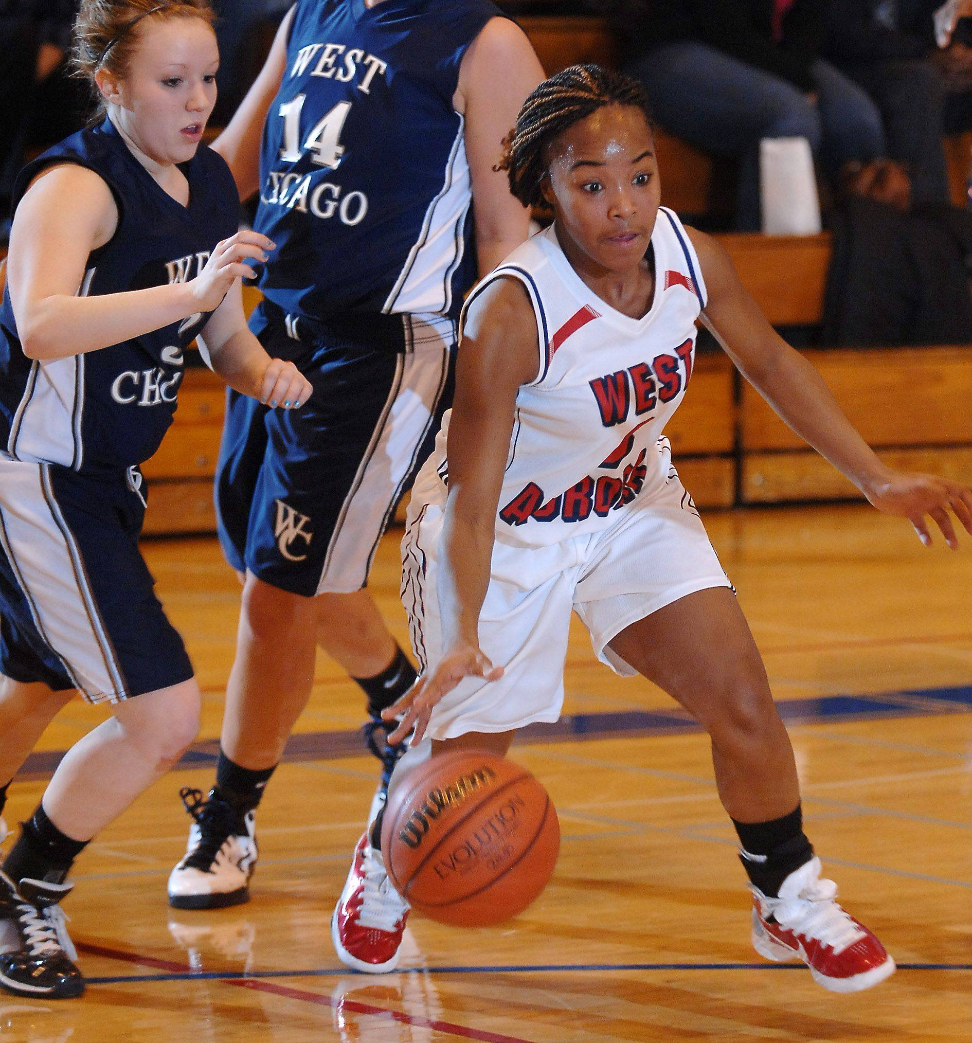 West Aurora's Dazmine Chaney drives past a pair of West Chicago defenders.