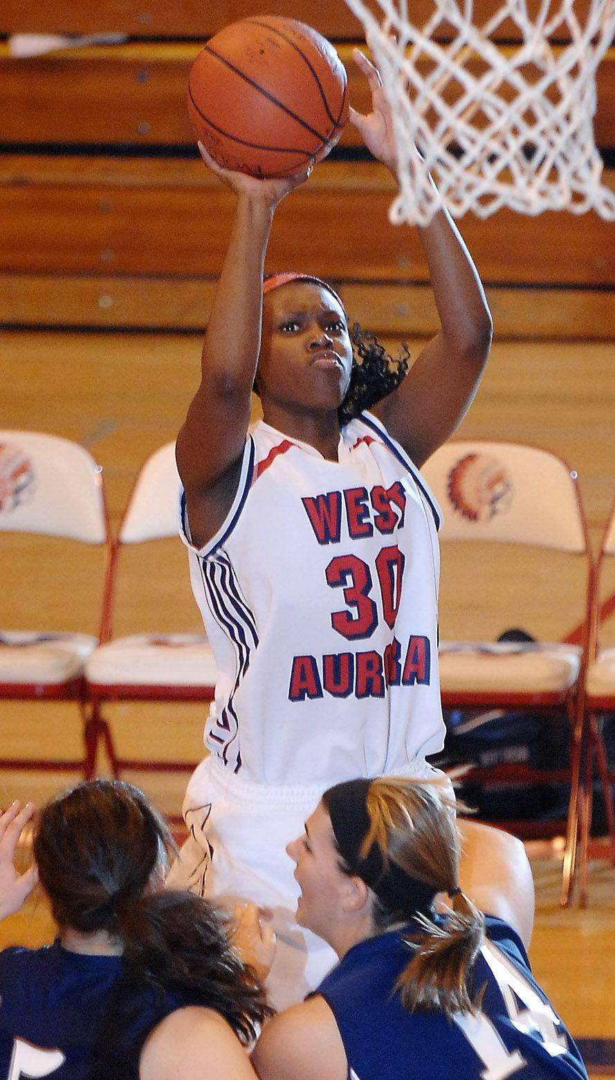 West Aurora's Royalle Brown launches a shot over a pair of West Chicago defenders.