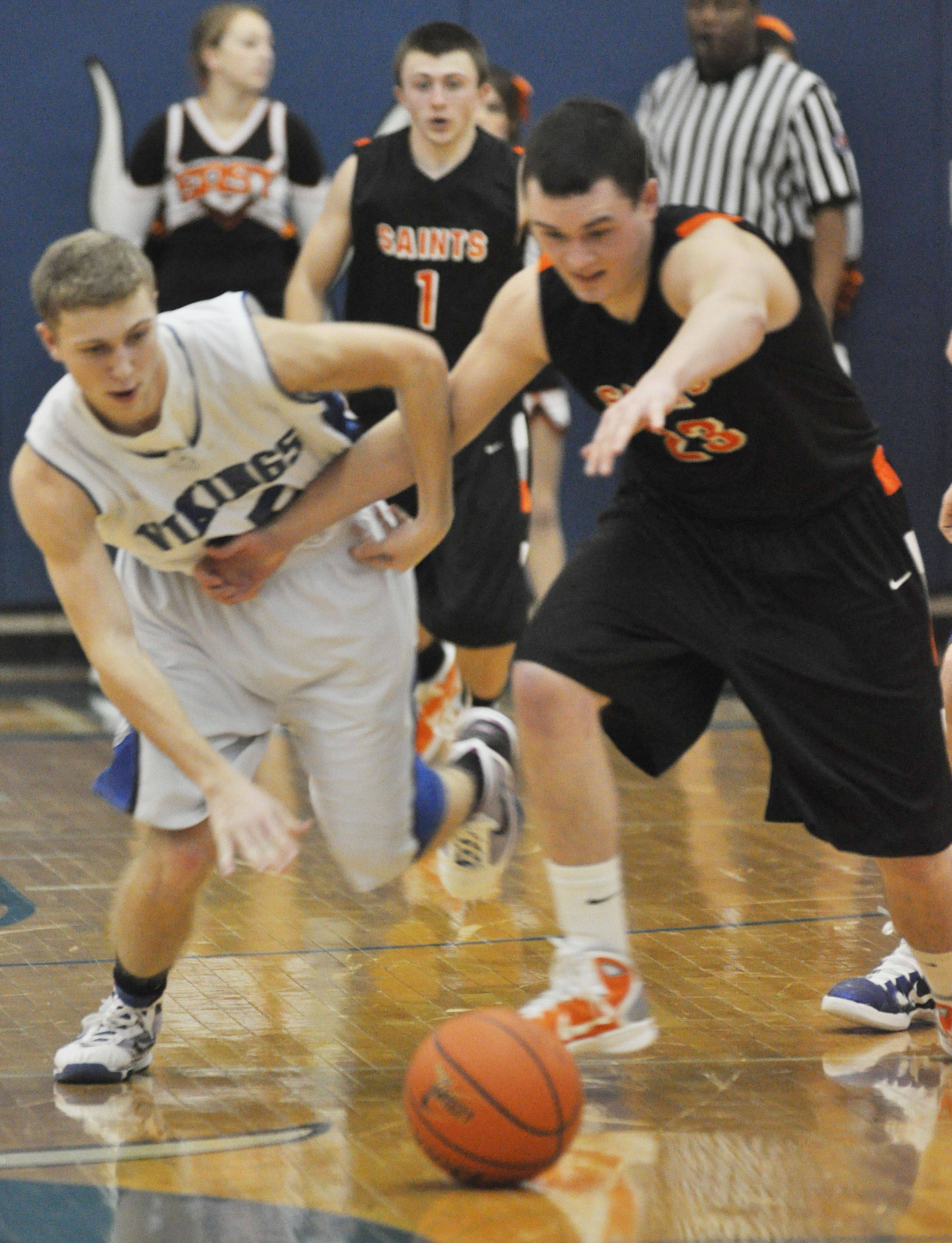 Phil Lorenz of Geneva and Johnny Hondlik of St. Charles East fight for the ball at Geneva High School Friday night.